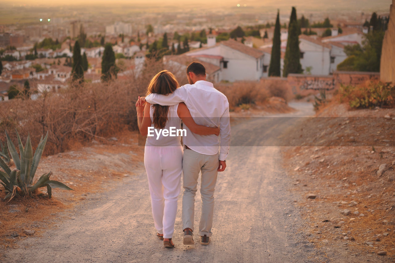full length, real people, built structure, women, building exterior, architecture, togetherness, rear view, lifestyles, two people, bonding, leisure activity, people, casual clothing, positive emotion, adult, emotion, city, love, nature, couple - relationship, outdoors, arm around, hairstyle, sister