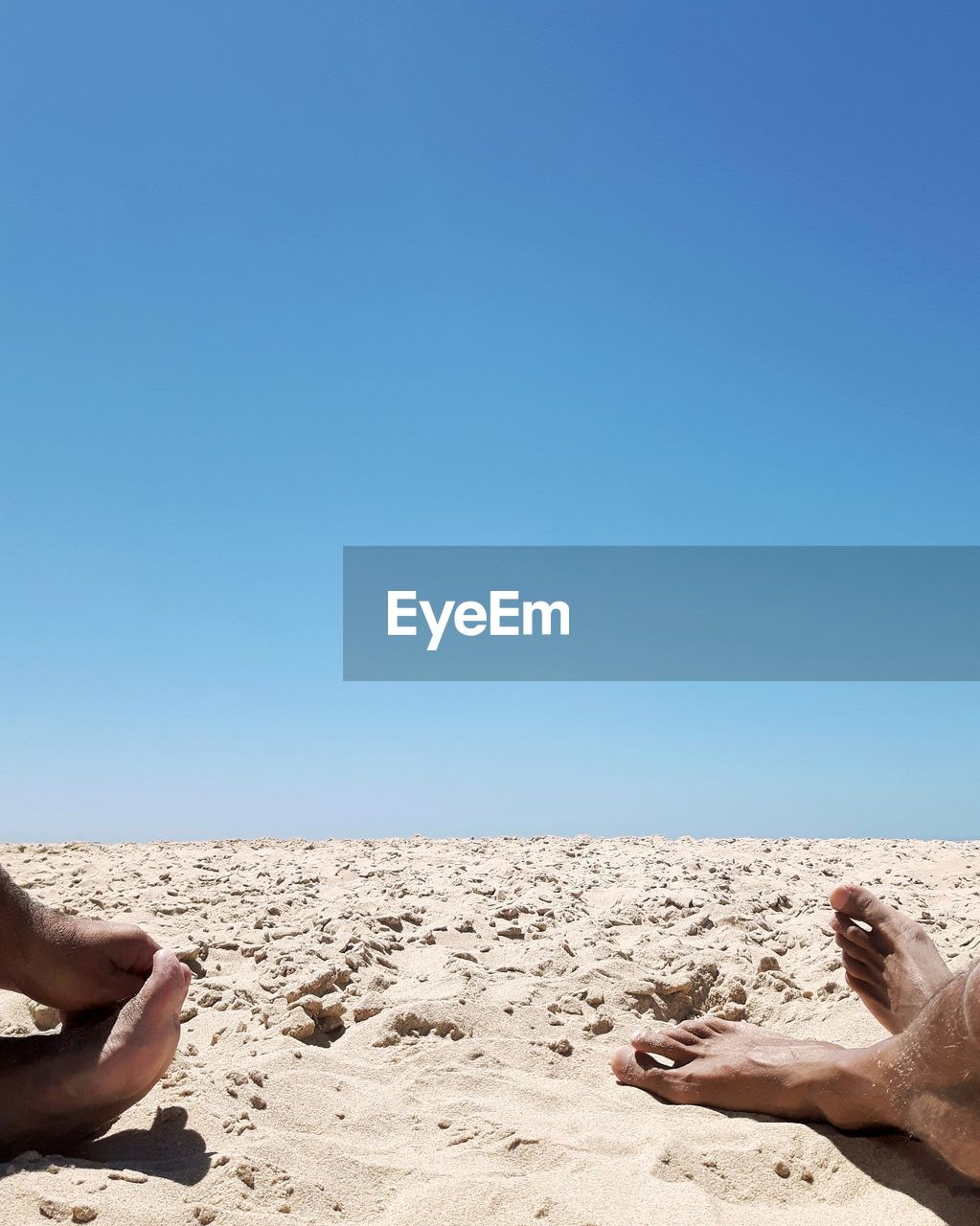 LOW SECTION OF MAN LYING ON SAND AT BEACH