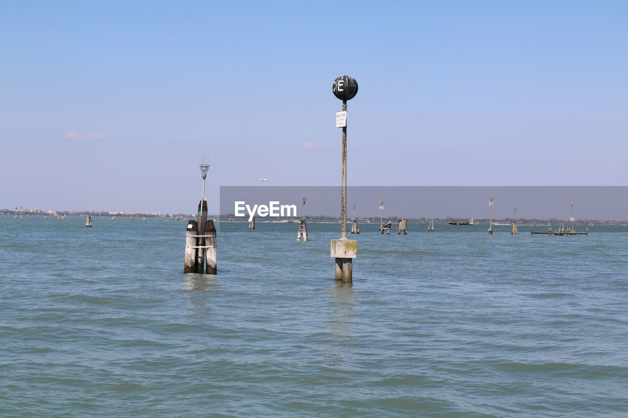 water, sea, waterfront, sky, nature, beauty in nature, scenics - nature, nautical vessel, day, no people, transportation, architecture, mode of transportation, outdoors, blue, built structure, clear sky, tranquil scene, travel, post, wooden post