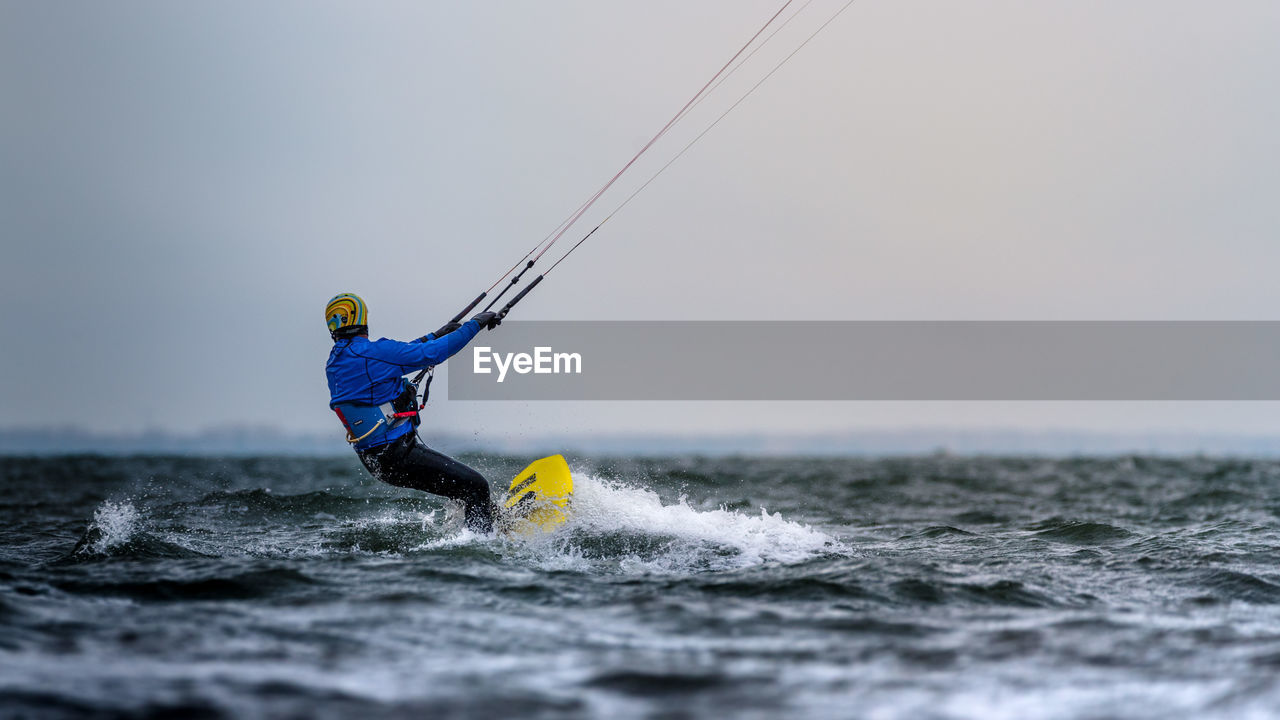 Man wakeboarding in sea against clear sky at dusk
