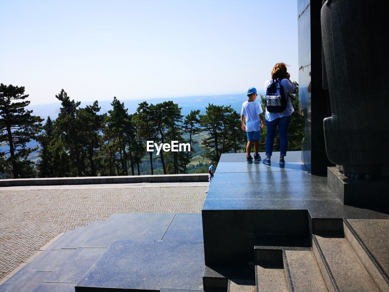Rear view of people standing on observation point against sky during sunny day
