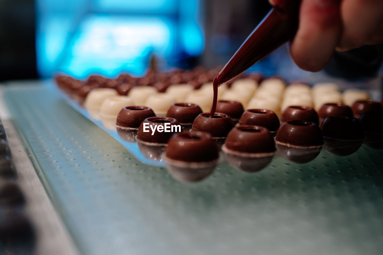 Hand filling pralines with chocolate