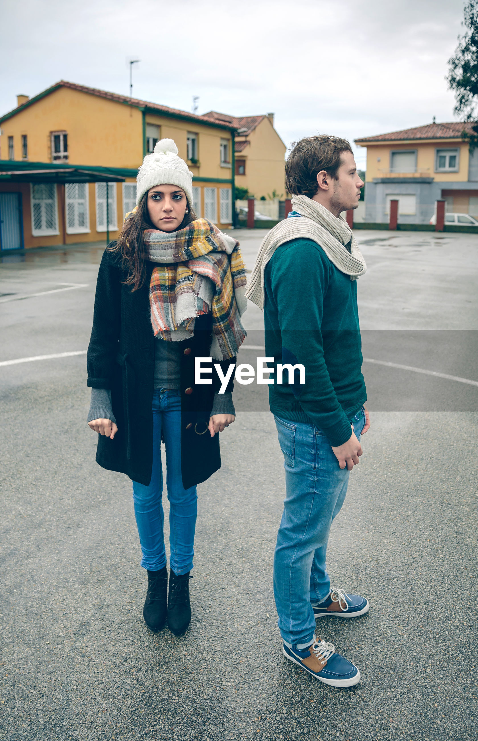 Full length of sad couple looking away while standing on road