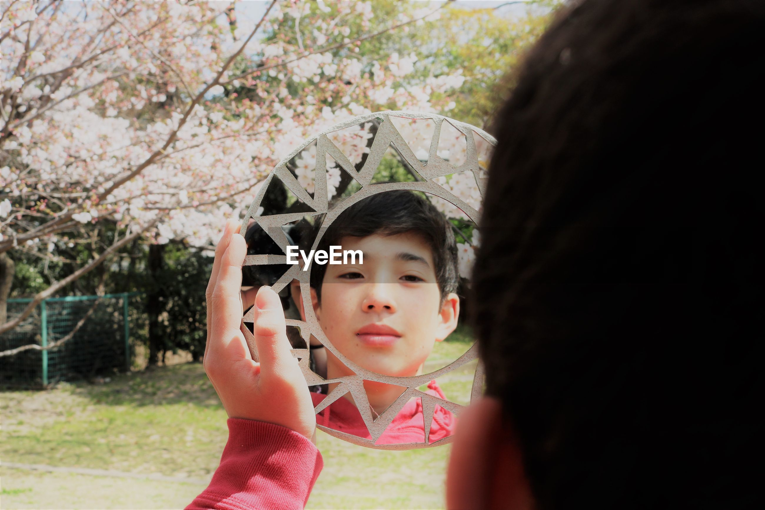 Close-up of boy looking in mirror at park