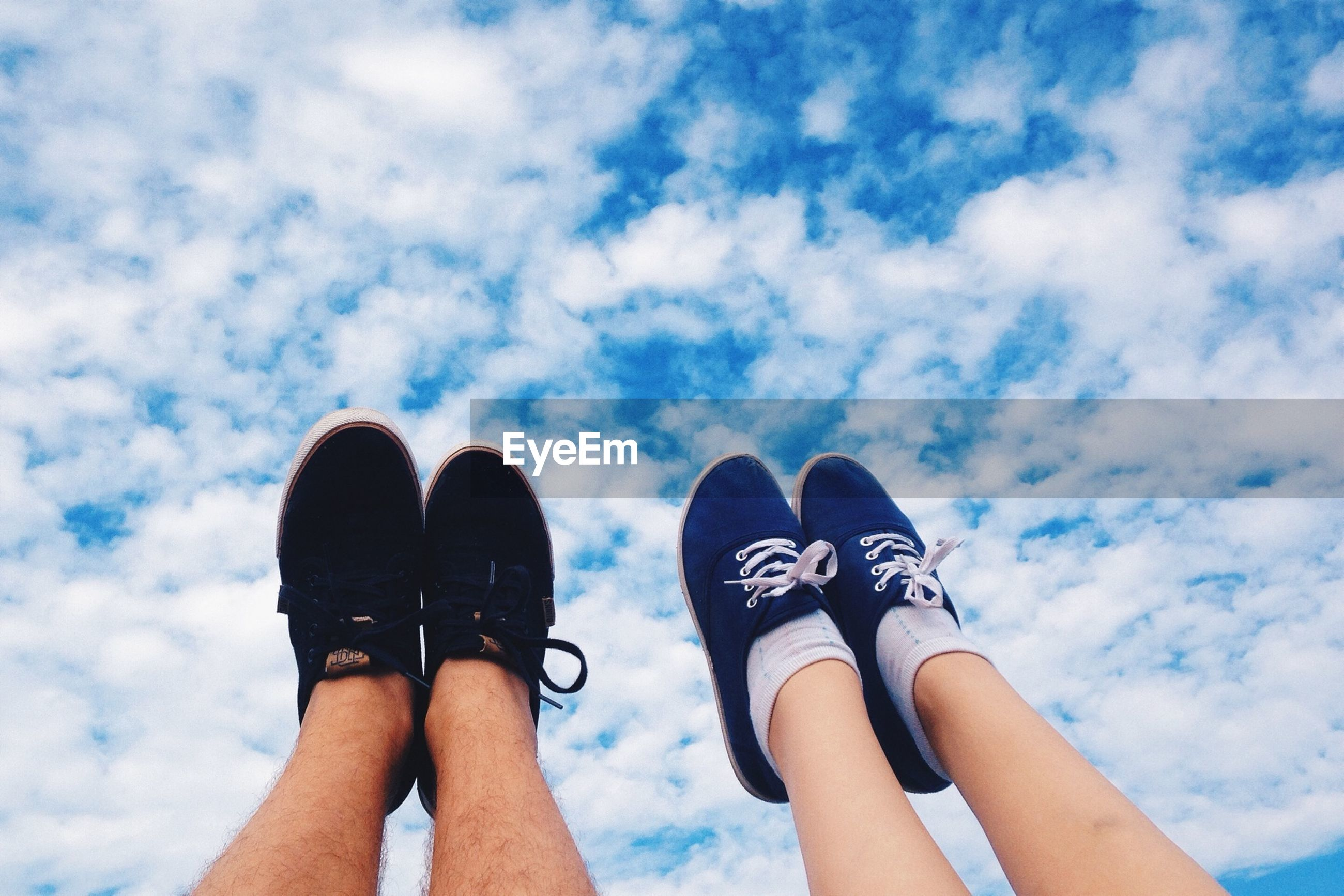 low section, person, personal perspective, lifestyles, leisure activity, togetherness, standing, human foot, sky, shoe, cloud - sky, relaxation, men, bonding, friendship