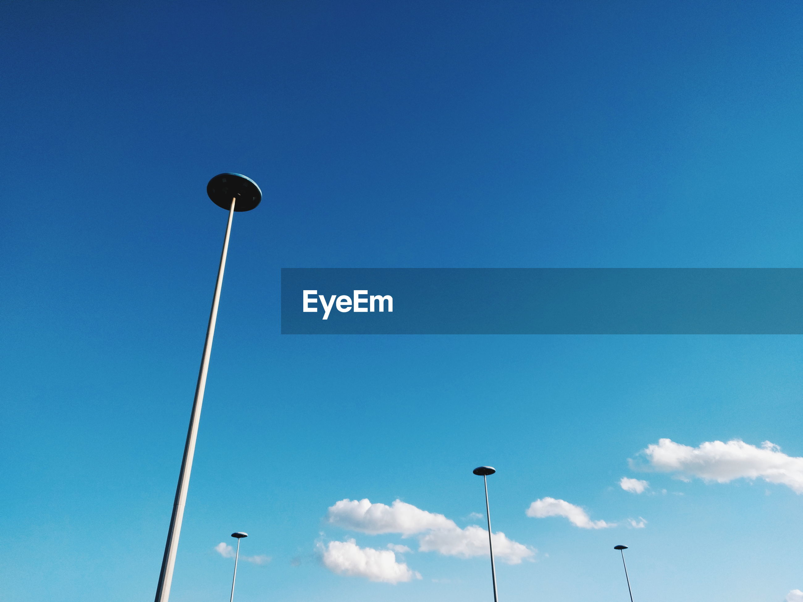 Low angle view of street lights against blue sky