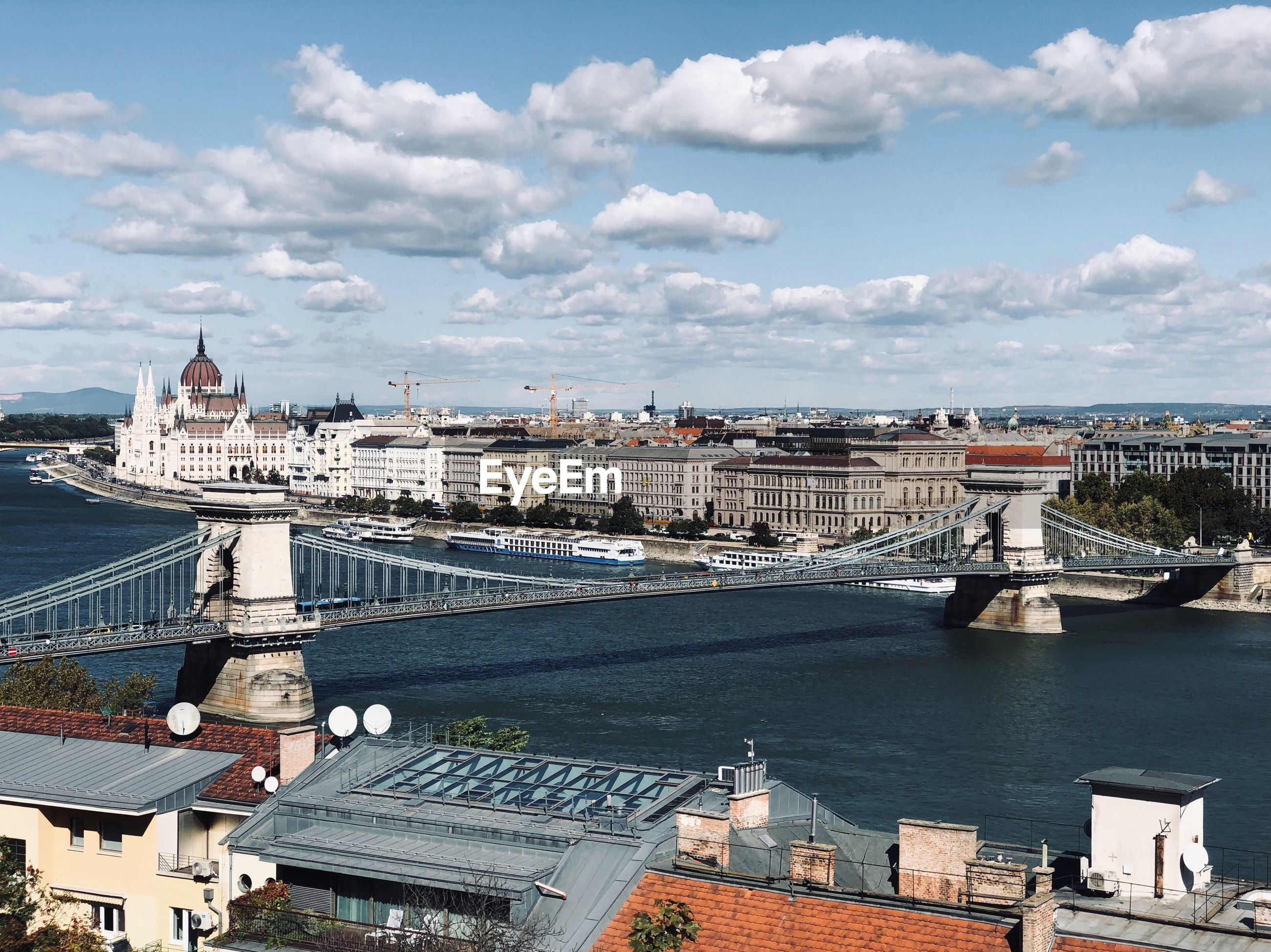 Szechenyi chain bridge over danube river in city on sunny day