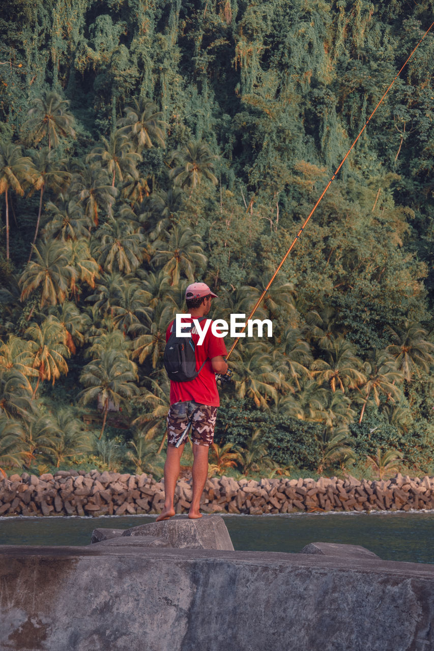 one person, full length, plant, tree, casual clothing, day, leisure activity, real people, nature, men, standing, outdoors, males, adventure, childhood, lifestyles, child, activity, shorts