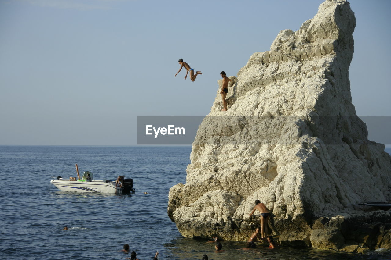 sea, rock - object, real people, water, leisure activity, nature, clear sky, day, men, beauty in nature, outdoors, lifestyles, horizon over water, scenics, adventure, sky, full length, sport, extreme sports, one person, bird, mammal, people