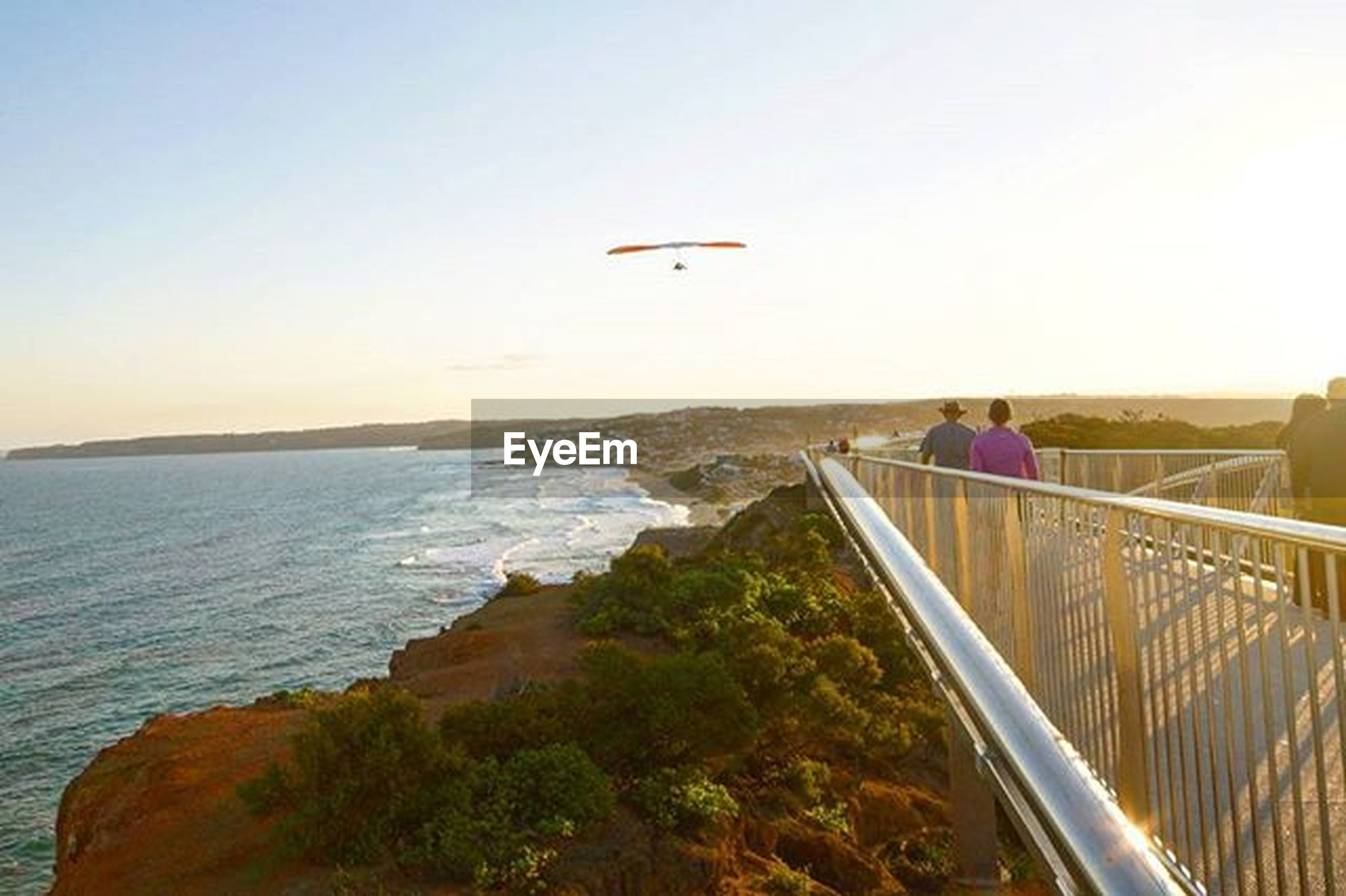 sea, clear sky, horizon over water, scenics, water, copy space, railing, tranquil scene, transportation, tranquility, beauty in nature, nature, leisure activity, mountain, men, lifestyles, sky, incidental people