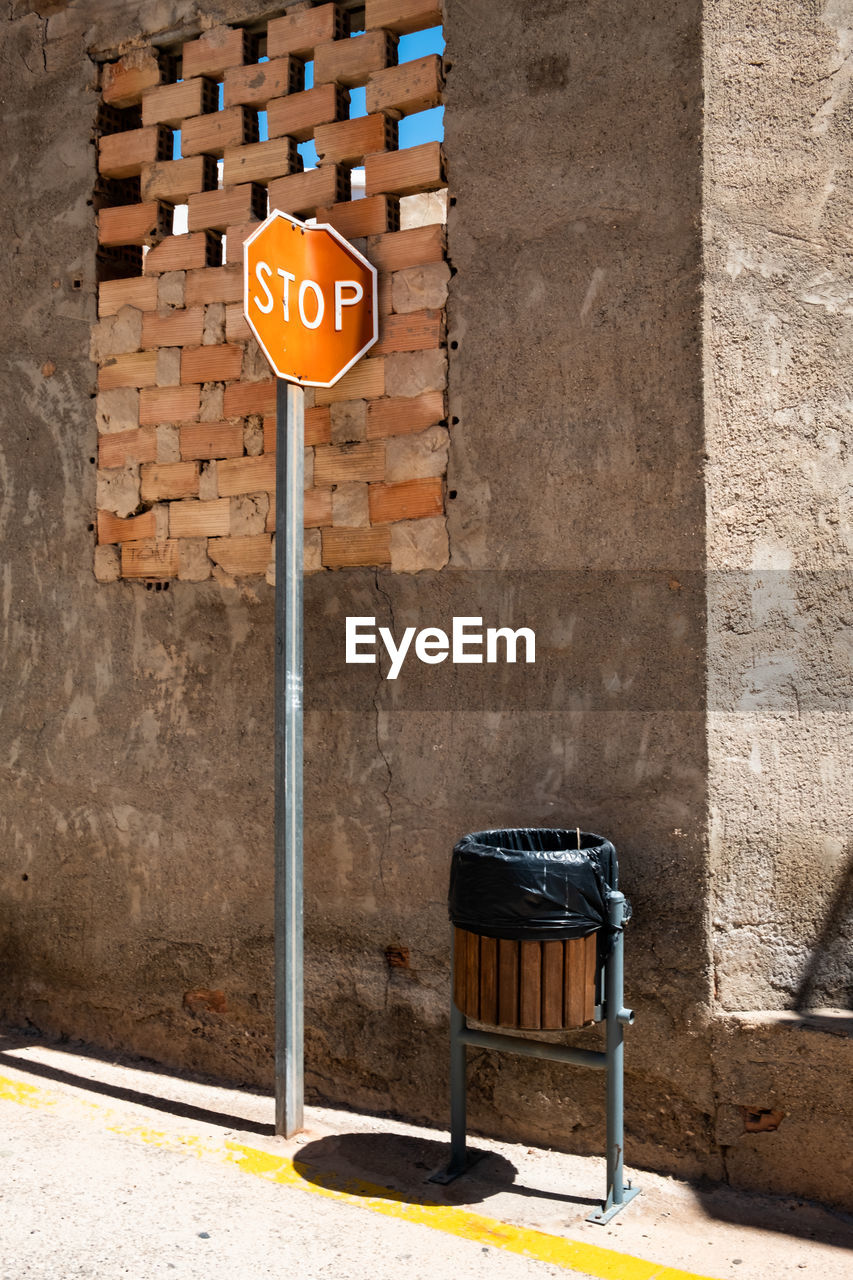 communication, sign, wall - building feature, architecture, no people, road sign, wall, built structure, text, seat, building exterior, day, absence, western script, chair, guidance, city, brick wall, road, brick