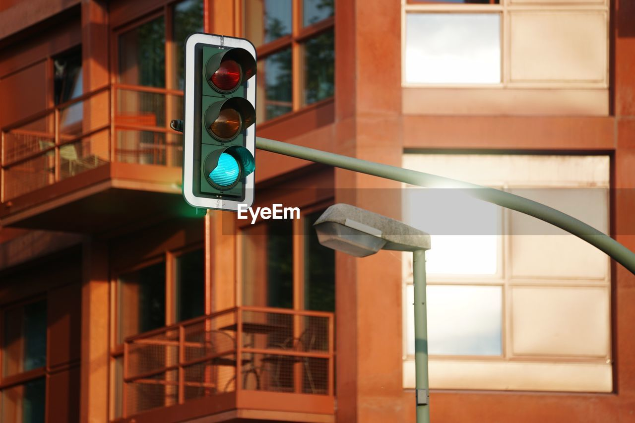 Low Angle View Of Stoplights Against Building