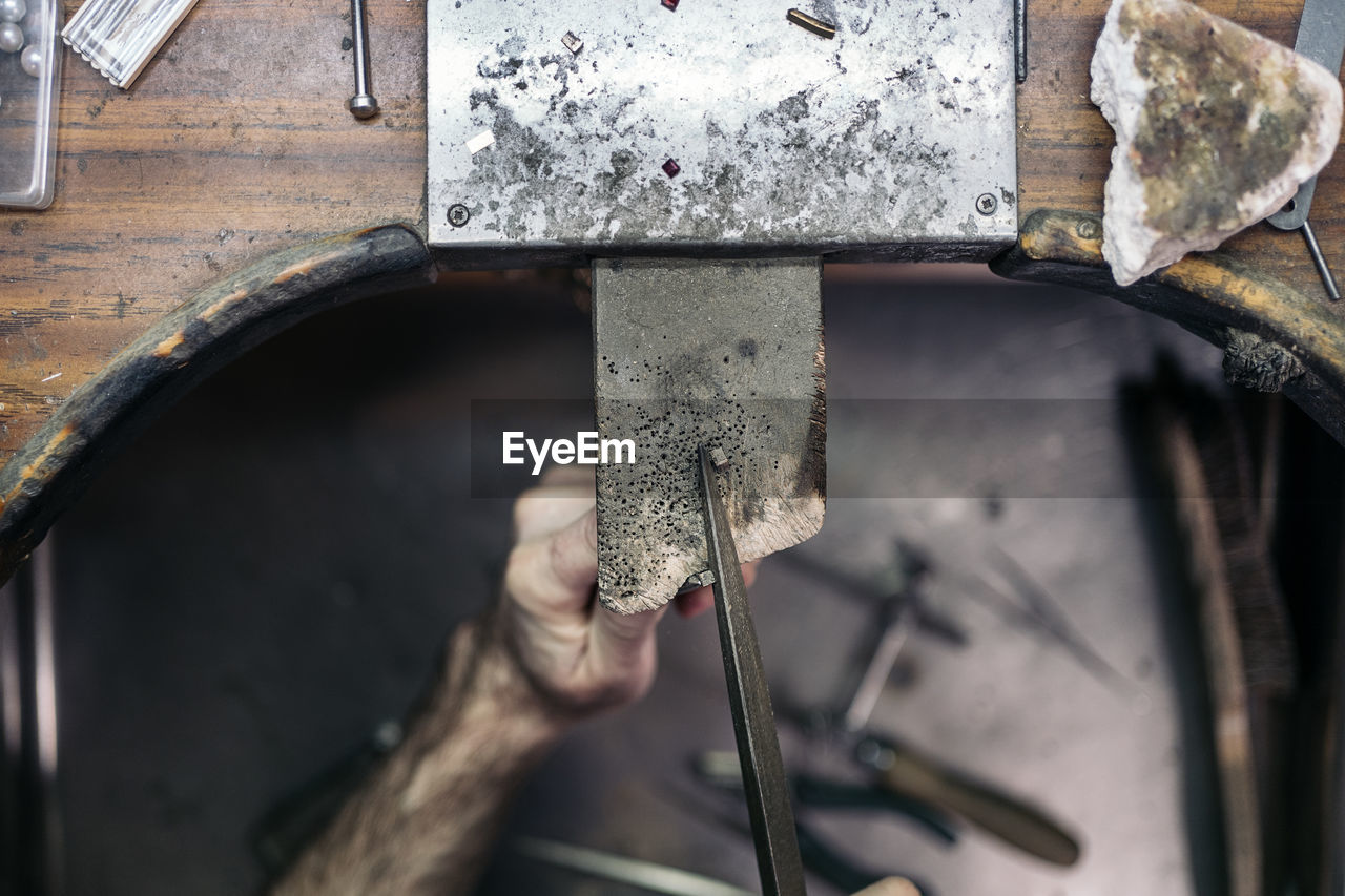 HIGH ANGLE VIEW OF PERSON HAND HOLDING RUSTY METAL