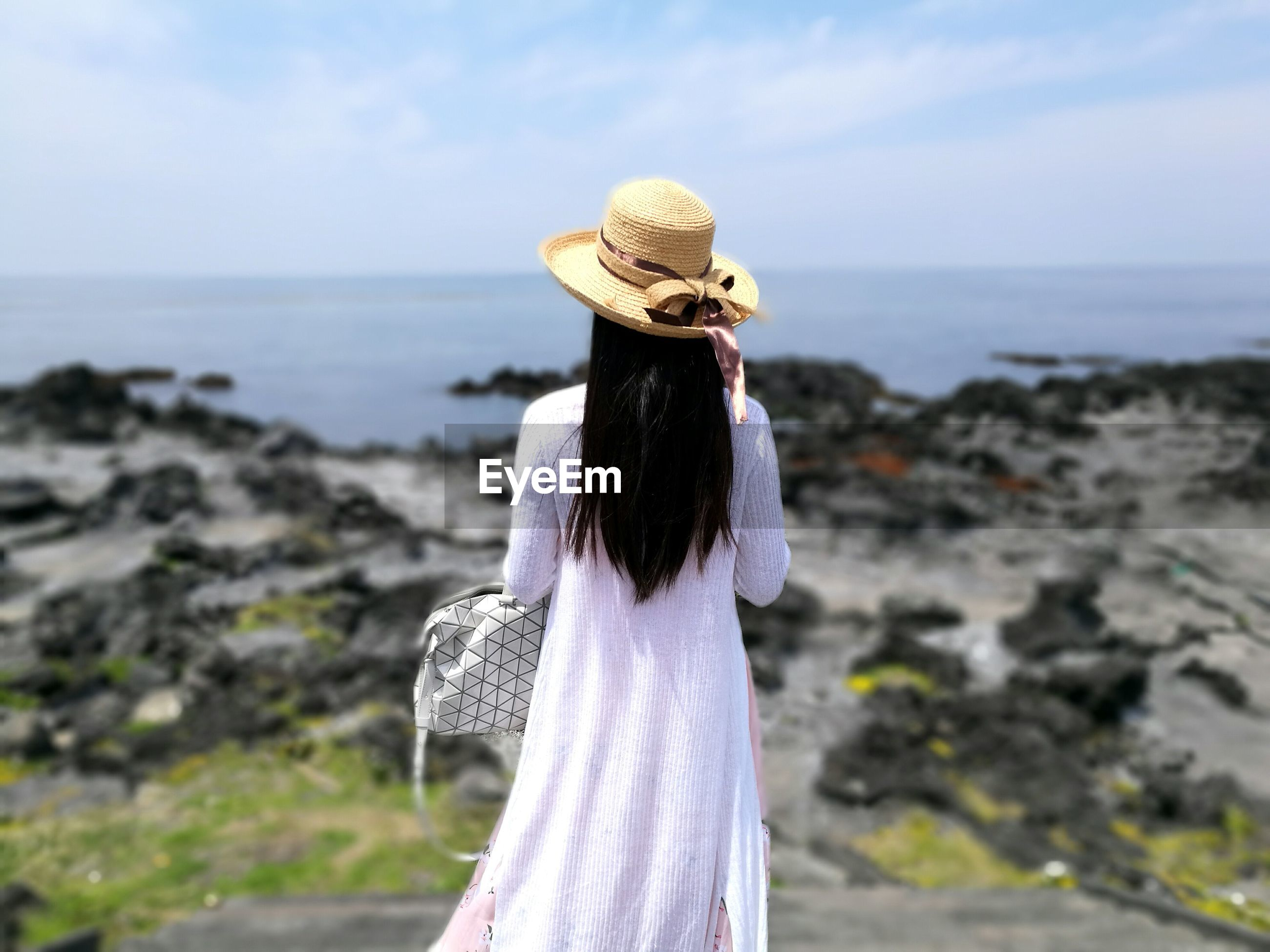 Rear view of woman standing on seashore