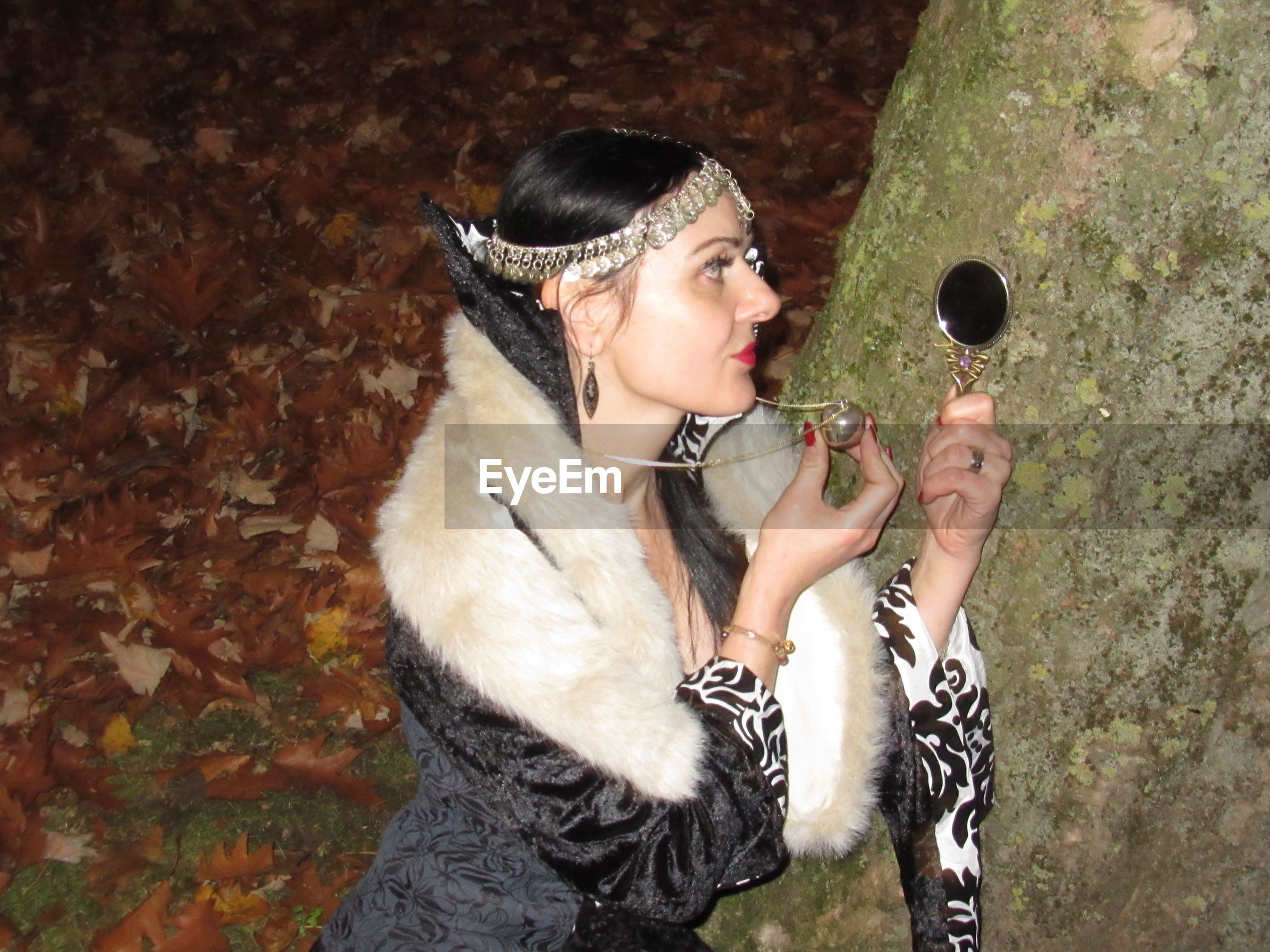 Young woman holding mirror and pendant by tree at night