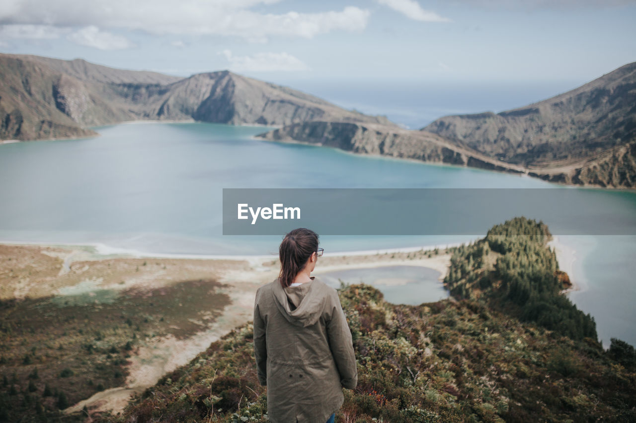 Rear view of woman on mountain looking at lake