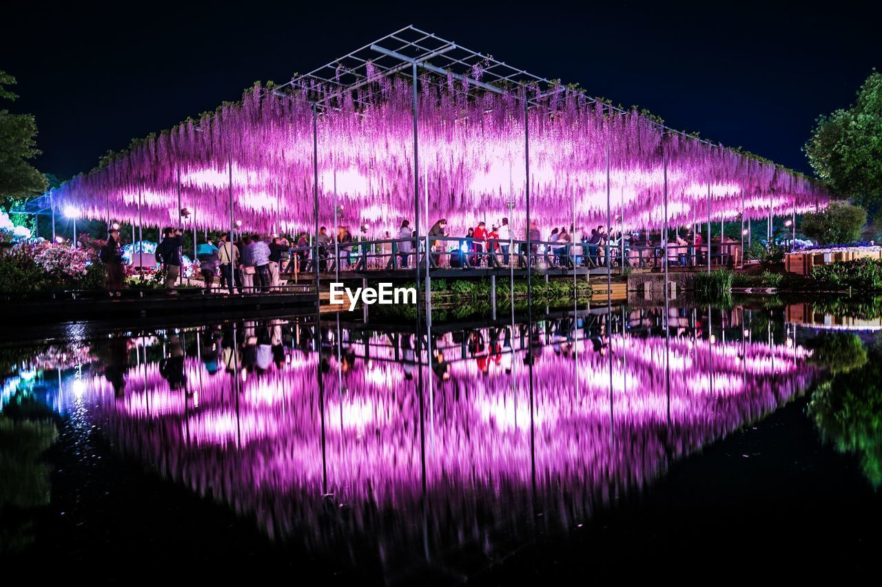 reflection, water, night, illuminated, waterfront, architecture, lake, pink color, nature, built structure, no people, purple, building exterior, sky, standing water, outdoors, symmetry, building