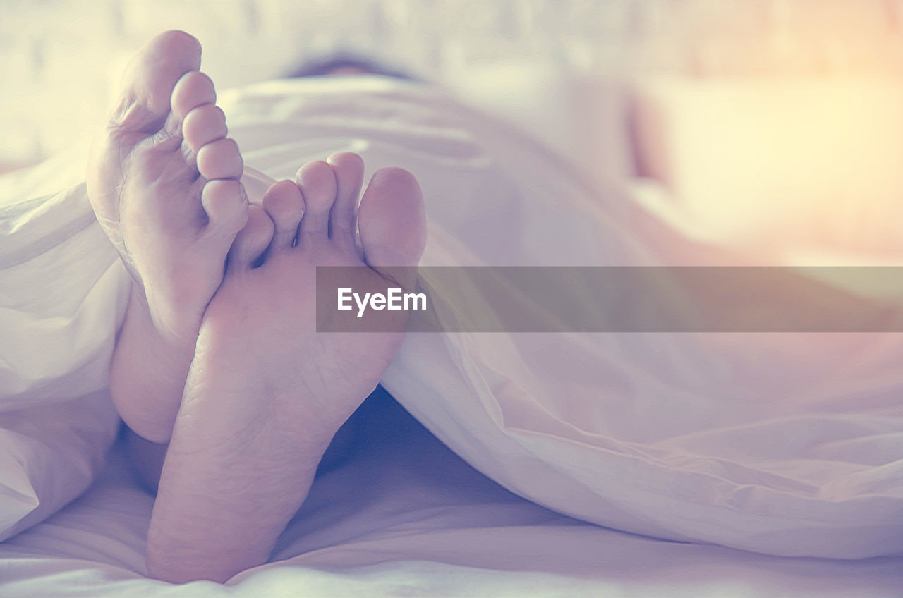 bed, barefoot, human foot, bedroom, low section, resting, comfortable, sole of foot, sheet, lying down, sleeping, relaxation, indoors, human leg, duvet, real people, home interior, close-up, lifestyles, one person, human body part, day, people