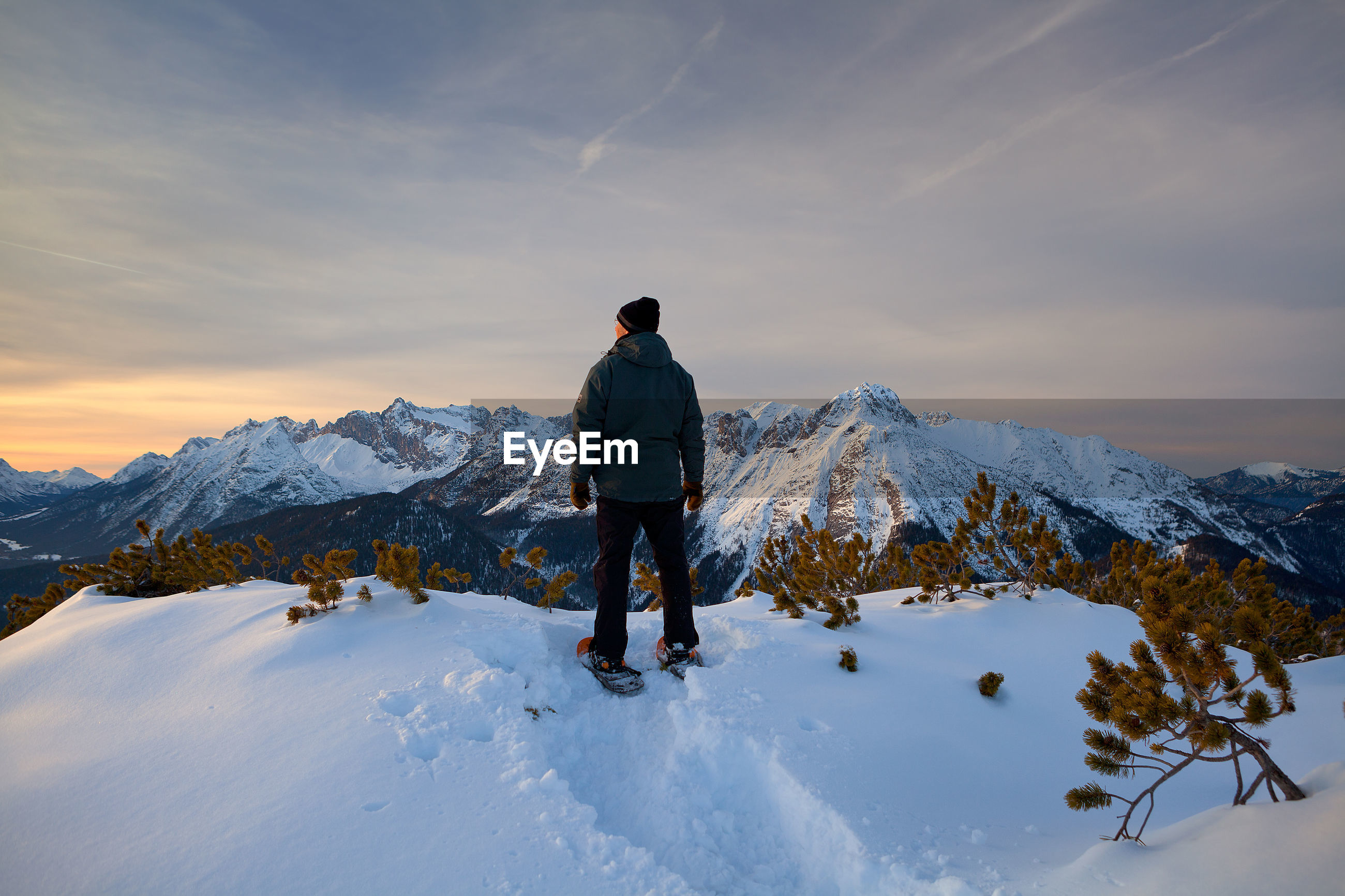 Rear view of man on snowcapped mountain against sky at dusk