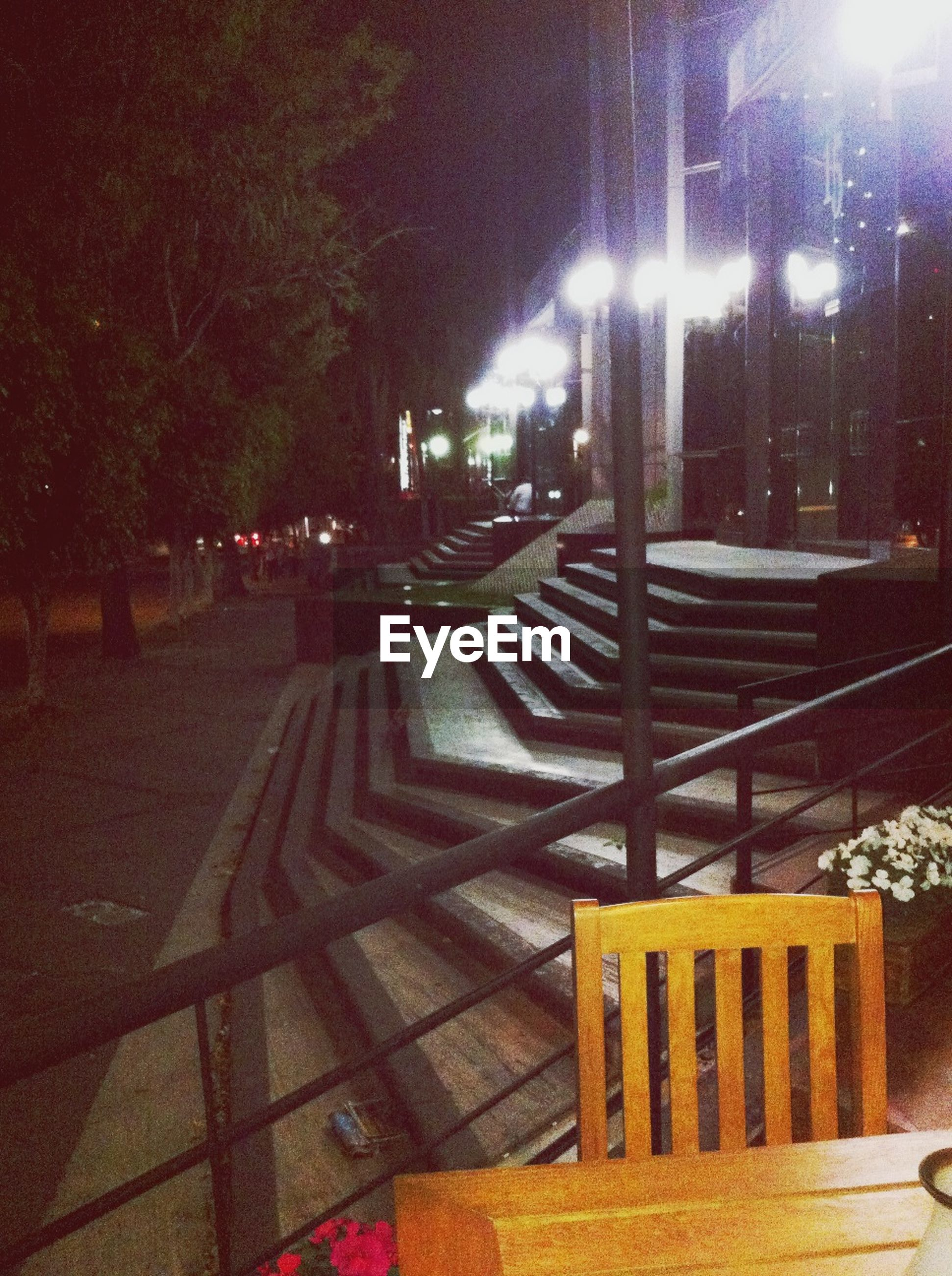 illuminated, night, empty, bench, absence, the way forward, lighting equipment, street light, railing, tree, seat, chair, no people, built structure, outdoors, city, transportation, high angle view, shadow, in a row