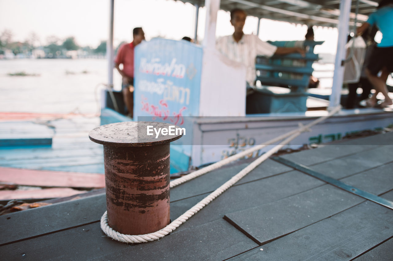 focus on foreground, day, incidental people, outdoors, rusty, metal, footpath, water, transportation, real people, nature, container, men, nautical vessel, sidewalk, close-up, mode of transportation, architecture, sunlight, selective focus