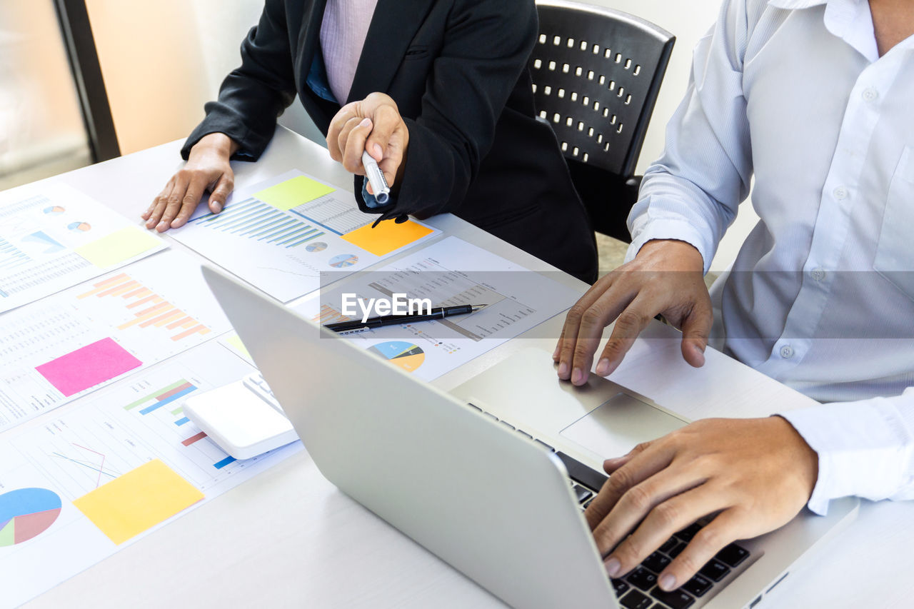 Midsection Of Colleagues Working At Desk In Office