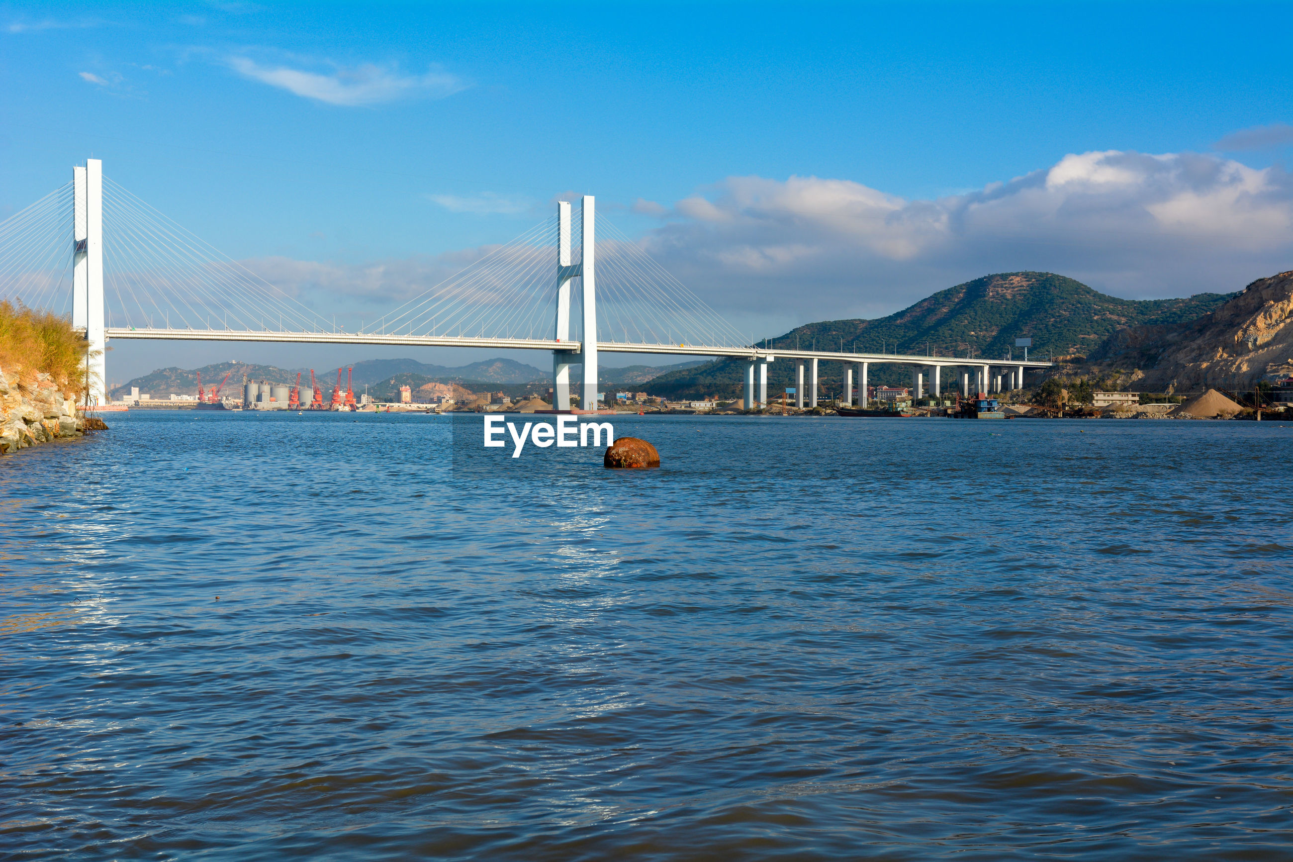 Distance shot of bridge over calm sea against sky
