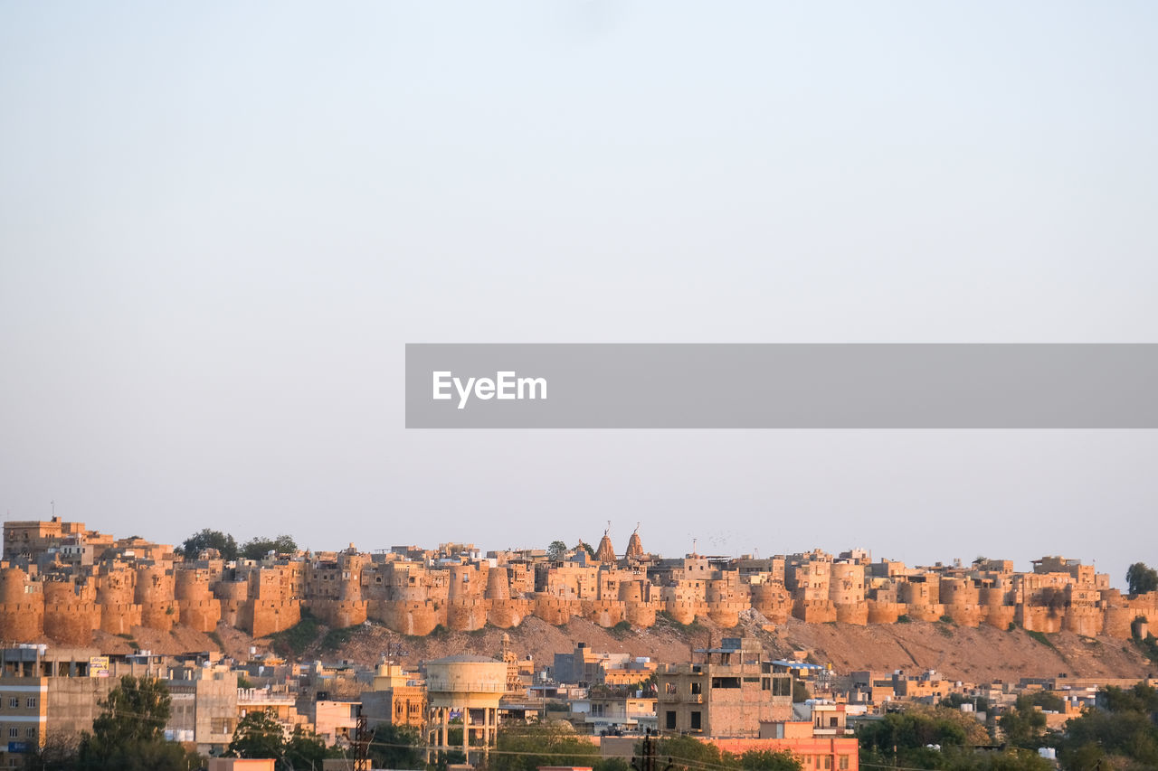 View of old fort of the golden city of jaisalmer against clear sky during blue hour