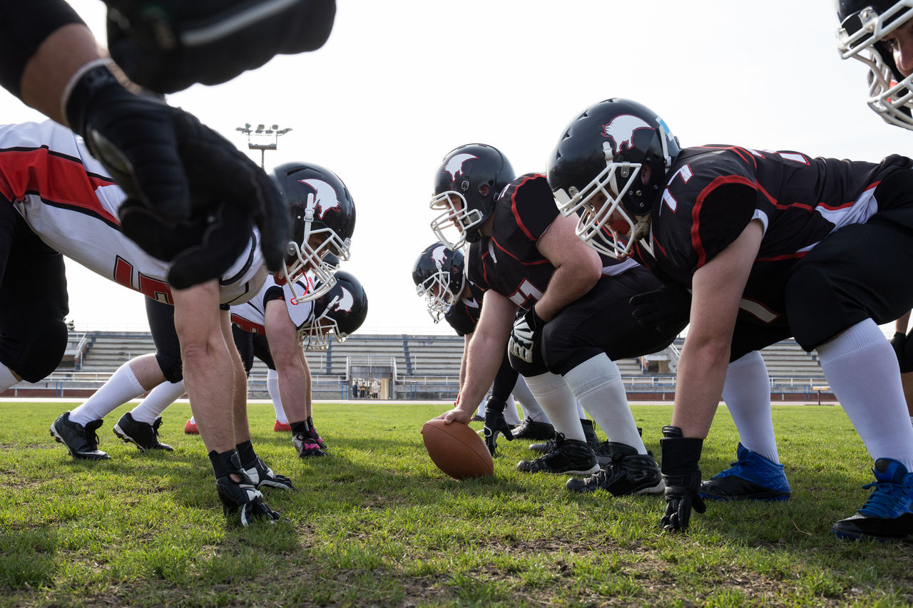 Low Angle View Of American Football Players With Ball Bending On Field