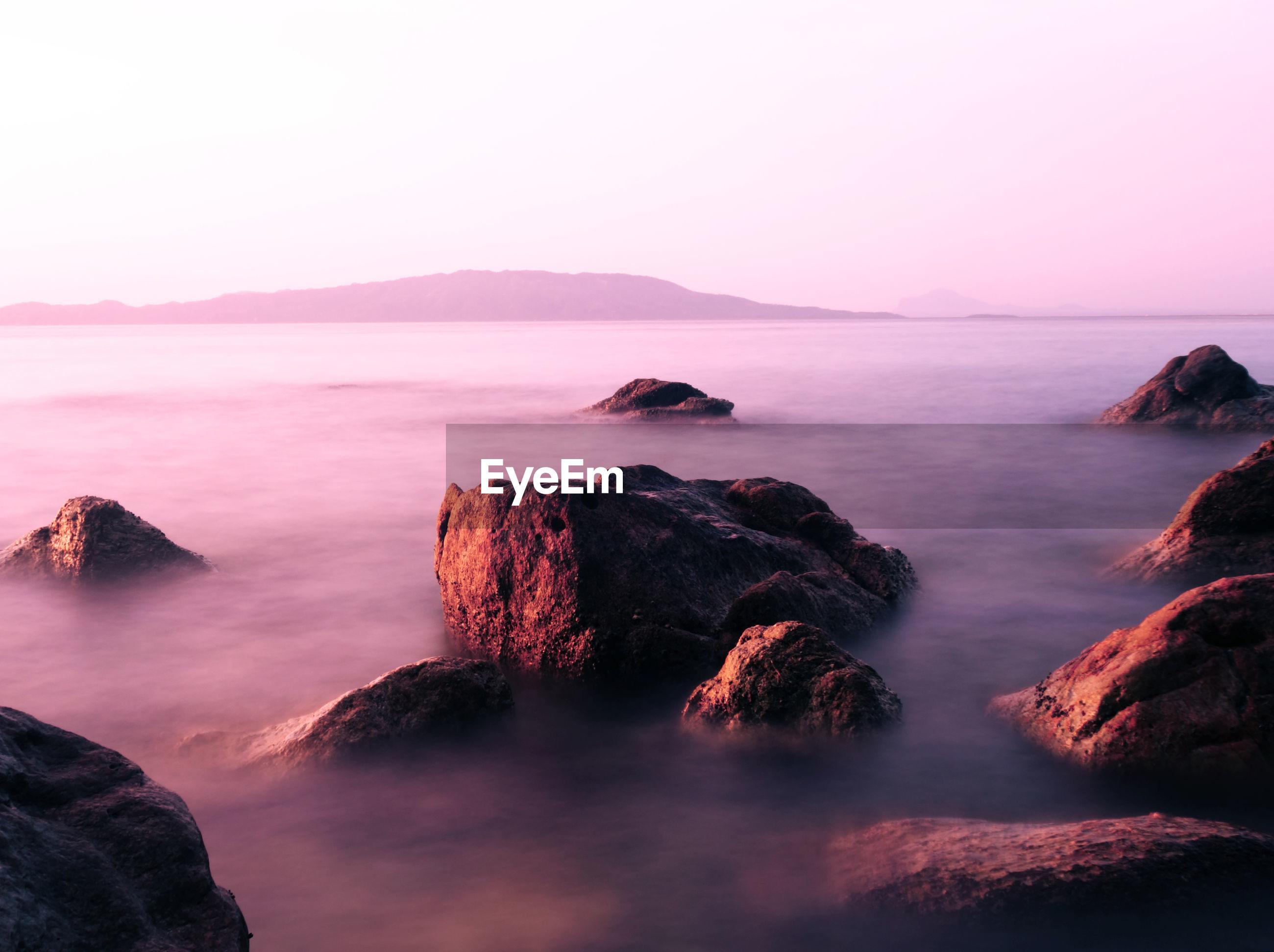 ROCKS IN SEA AGAINST CLEAR SKY