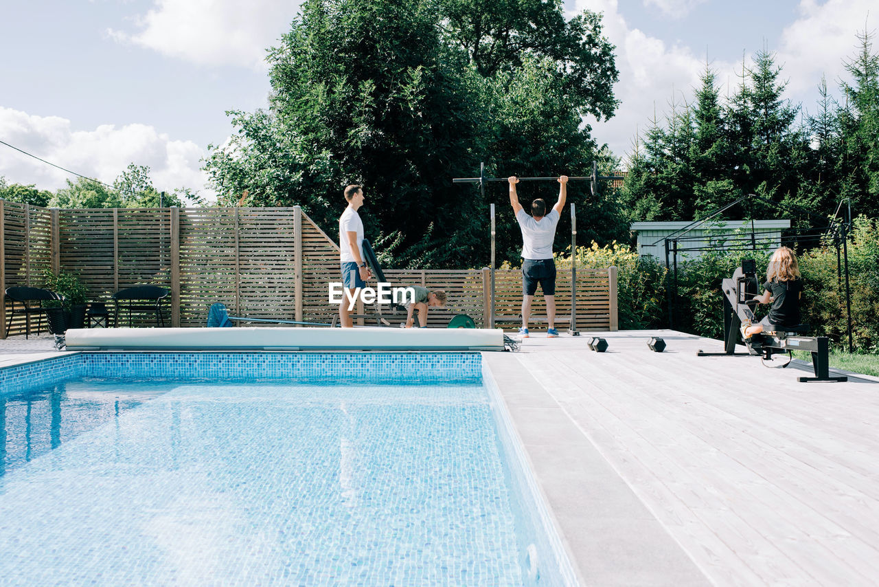 PEOPLE AT SWIMMING POOL BY TREES AGAINST SKY