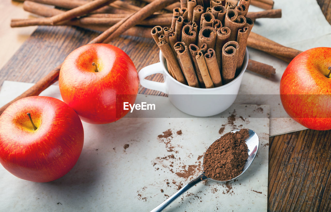 High angle view of apples with cinnamons in cup on table