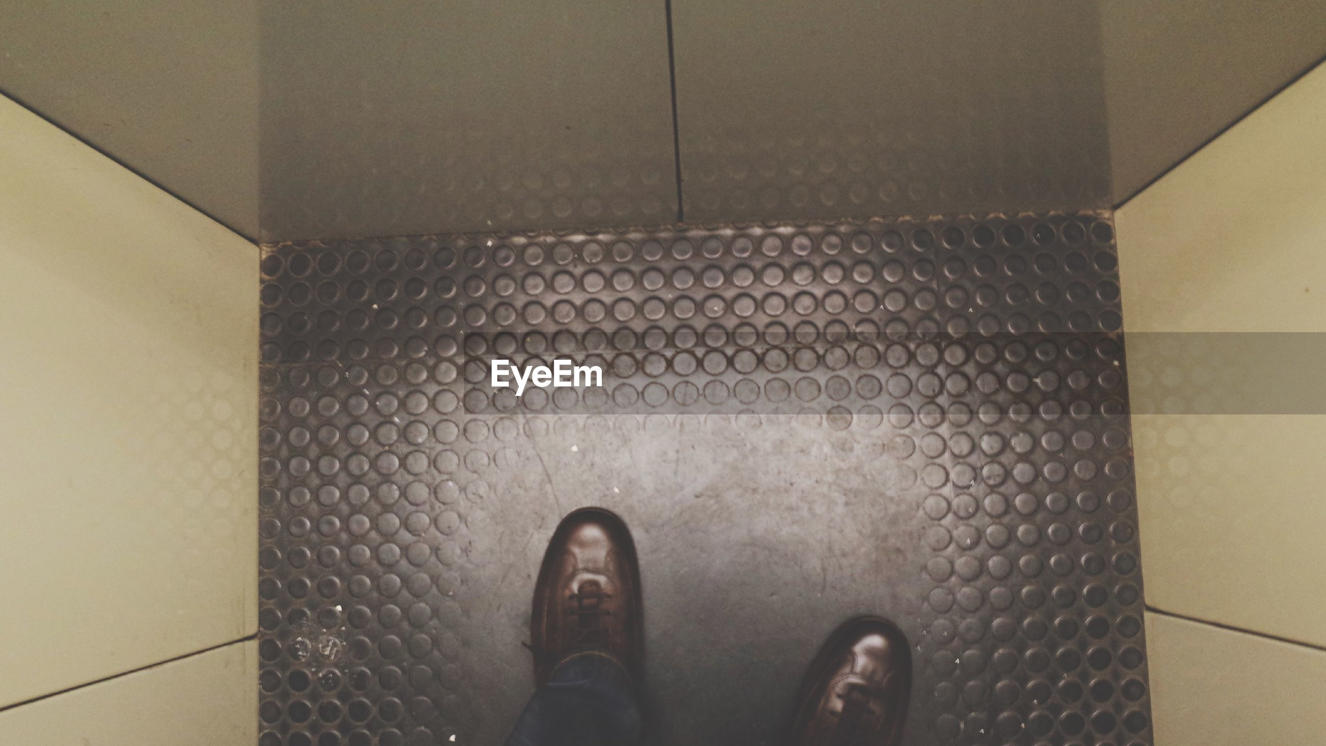 Low section of person standing in elevator