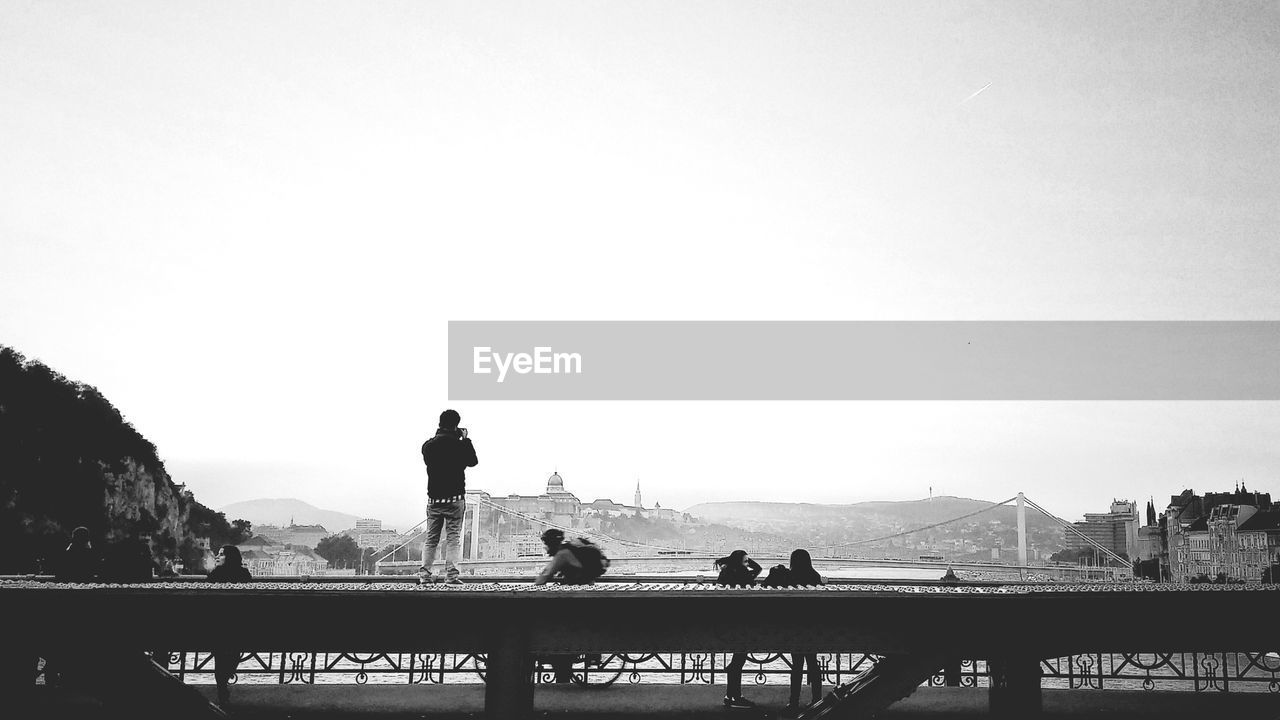 Rear view of man standing on bridge railing against clear sky