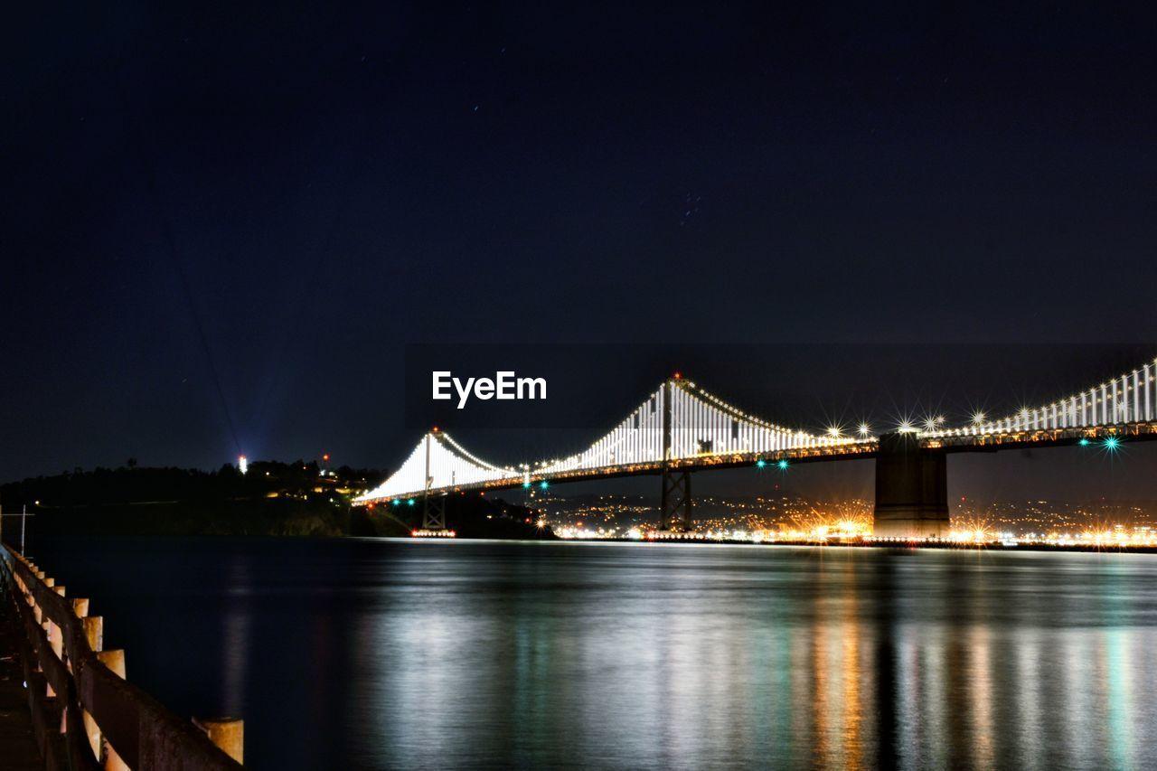 Illuminated Bridge Over Calm River At Night