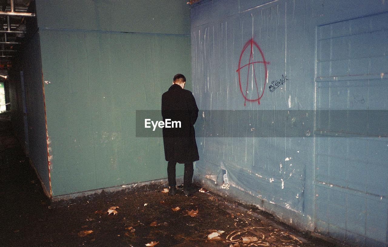 Man Urinating In Corner Of Building