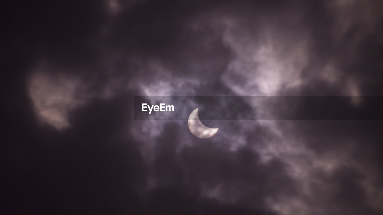 Partial Solar Eclipse In Cloudy Sky