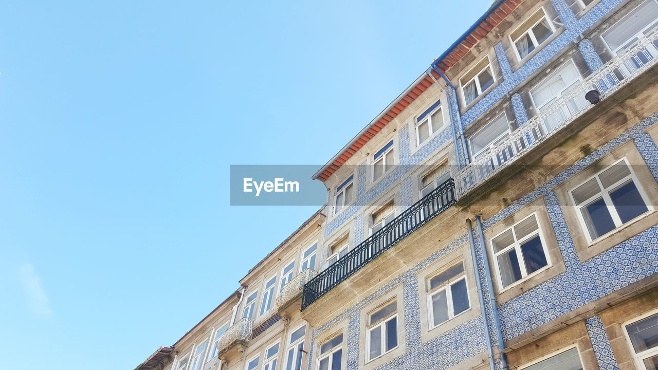 built structure, building exterior, architecture, sky, low angle view, window, building, clear sky, no people, residential district, day, blue, nature, copy space, outdoors, sunlight, city, glass - material, apartment, balcony
