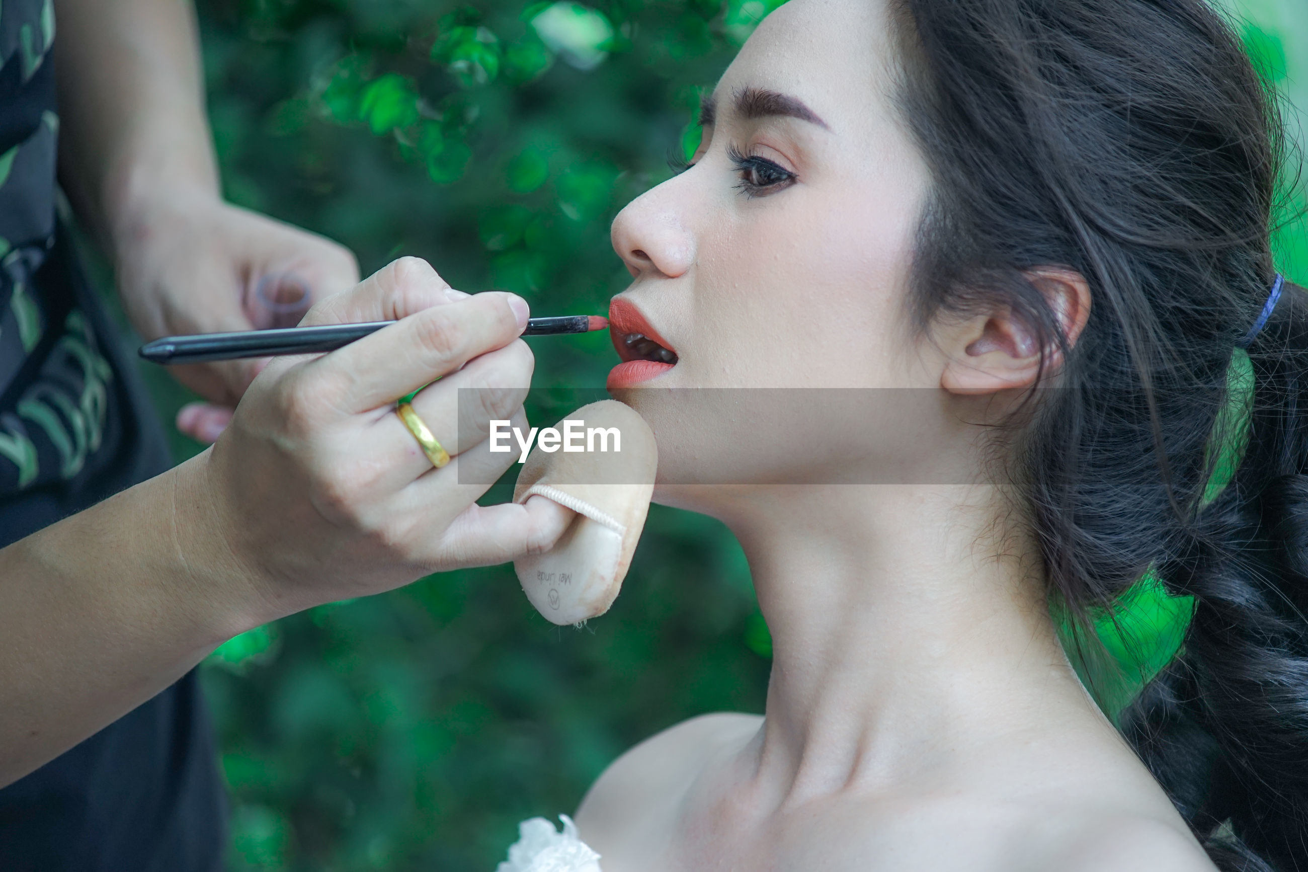 Close-up of person applying make-up on woman face