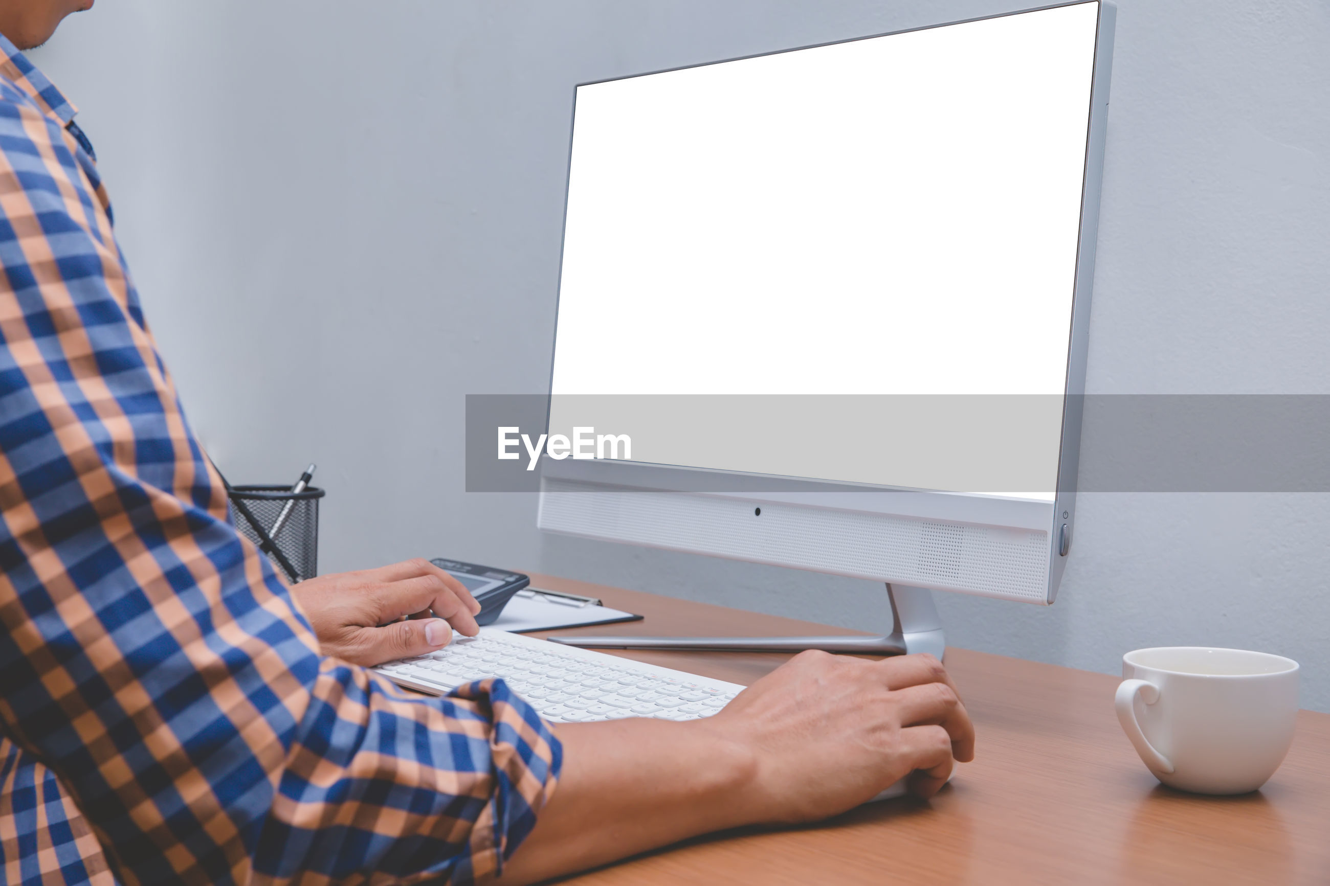 Midsection of man using desktop pc on table