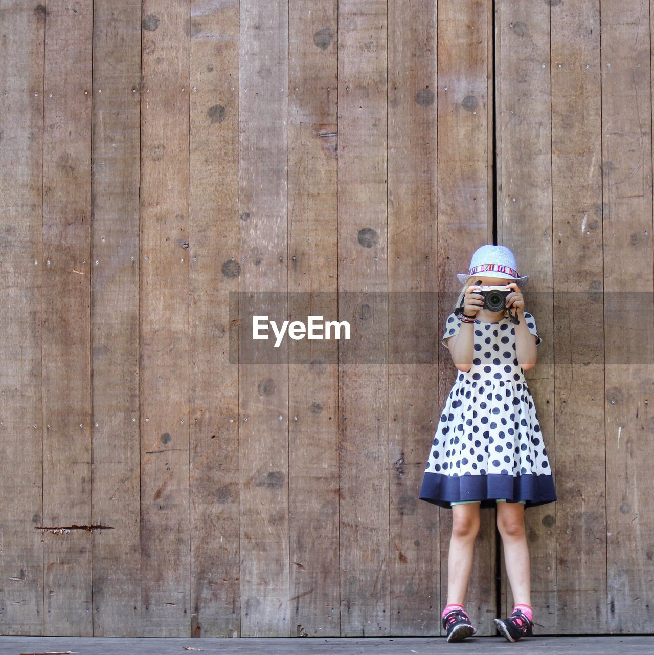 Girl Photographing While Standing Against Wooden Wall