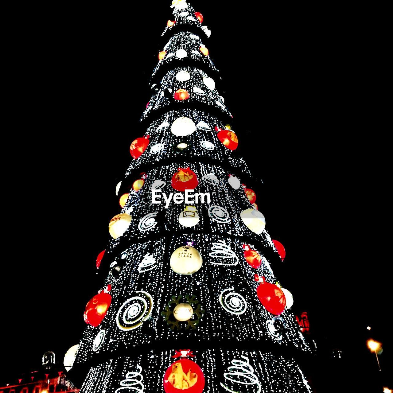 christmas, celebration, christmas tree, decoration, christmas decoration, night, tradition, illuminated, low angle view, christmas lights, tree topper, christmas ornament, black background, no people, vacations, holiday - event, studio shot, close-up, outdoors