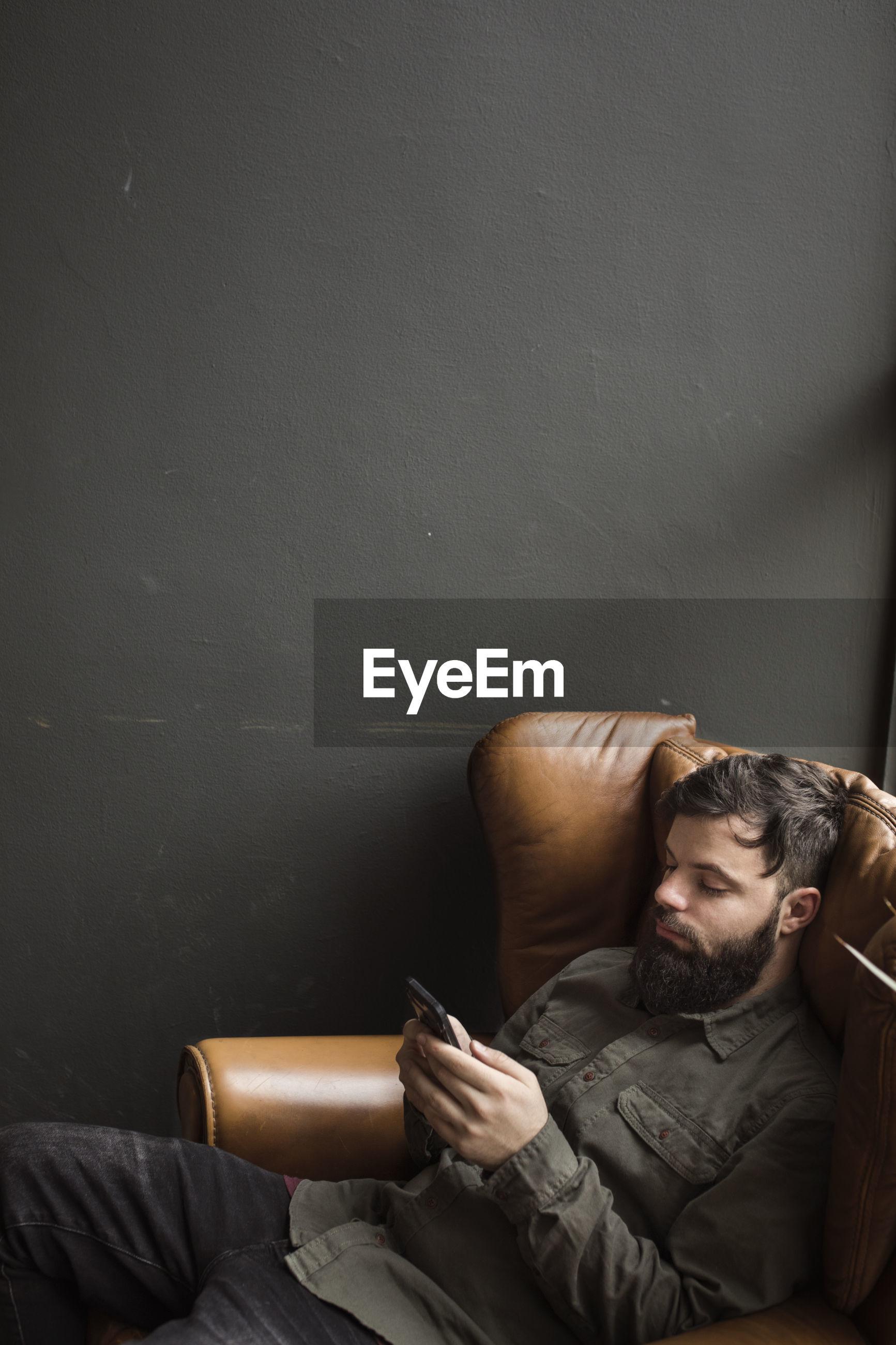 Man using mobile phone on sofa
