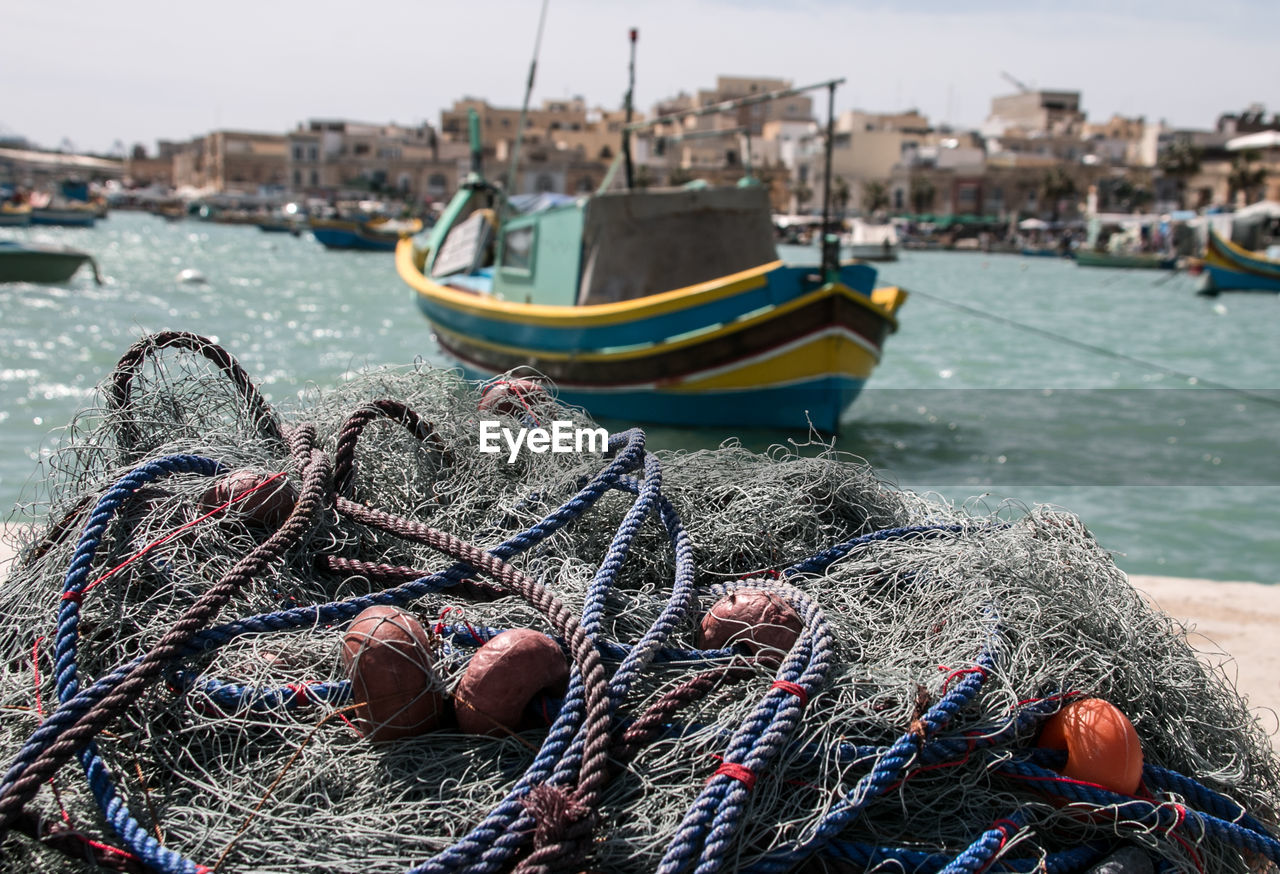nautical vessel, transportation, rope, mode of transportation, water, fishing net, fishing industry, fishing, harbor, focus on foreground, moored, sea, commercial fishing net, day, nature, buoy, no people, rod, fishing rod, outdoors, fishing boat, port