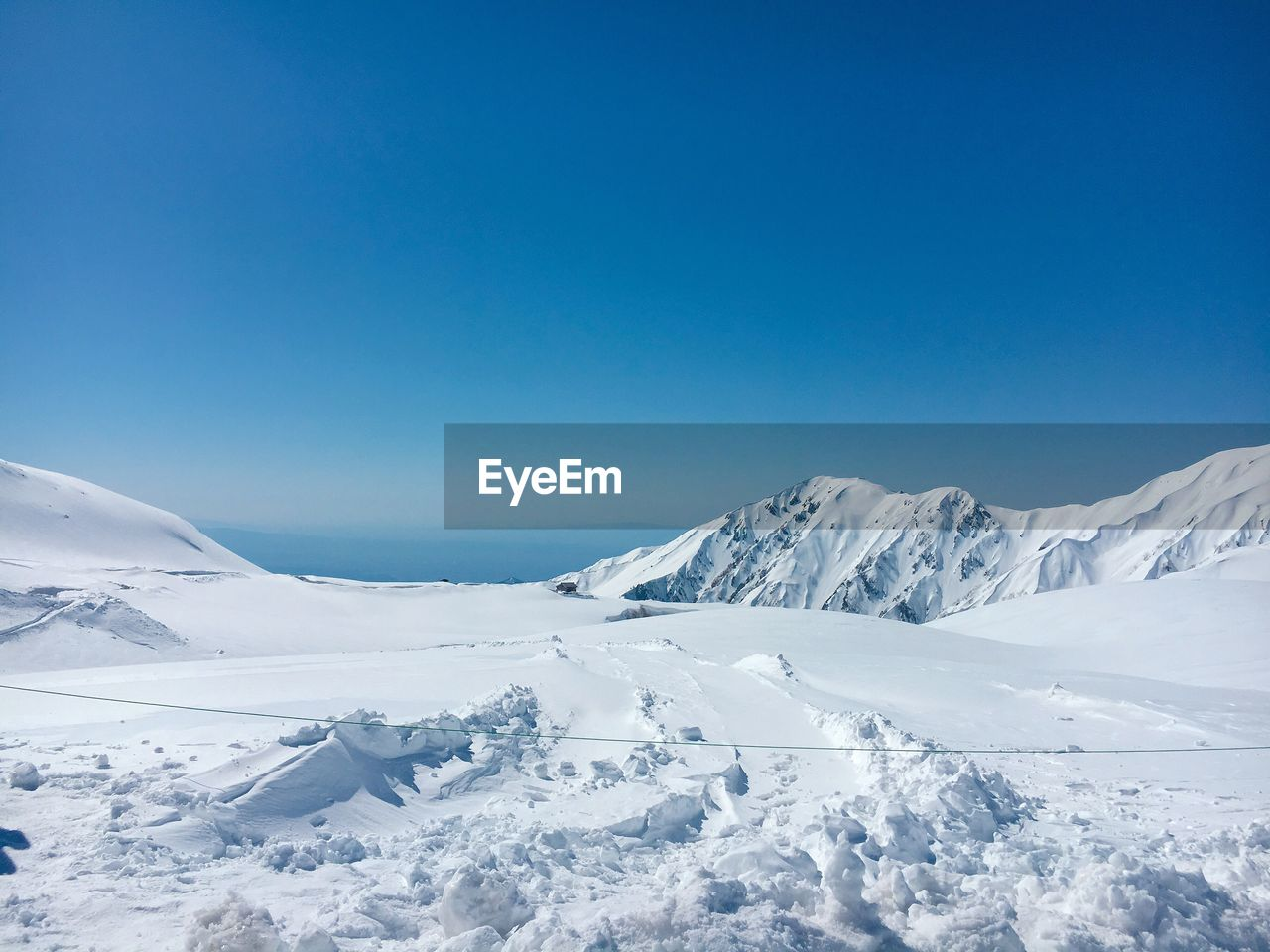 winter, snow, cold temperature, sky, blue, beauty in nature, tranquil scene, scenics - nature, tranquility, copy space, clear sky, mountain, white color, environment, nature, non-urban scene, day, no people, snowcapped mountain, extreme weather, mountain peak