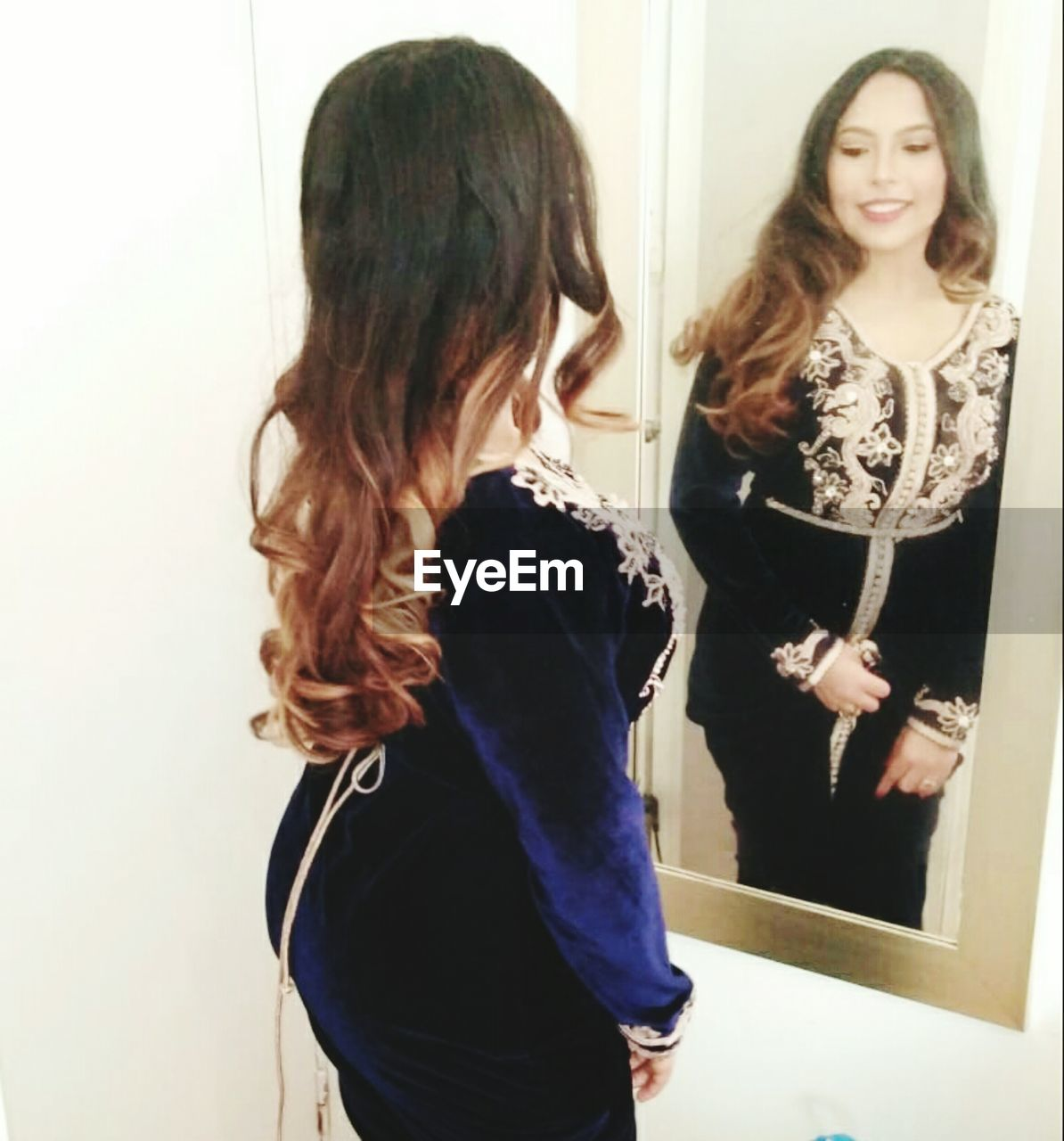 REAR VIEW OF WOMAN STANDING IN FRONT OF A YOUNG WOMEN