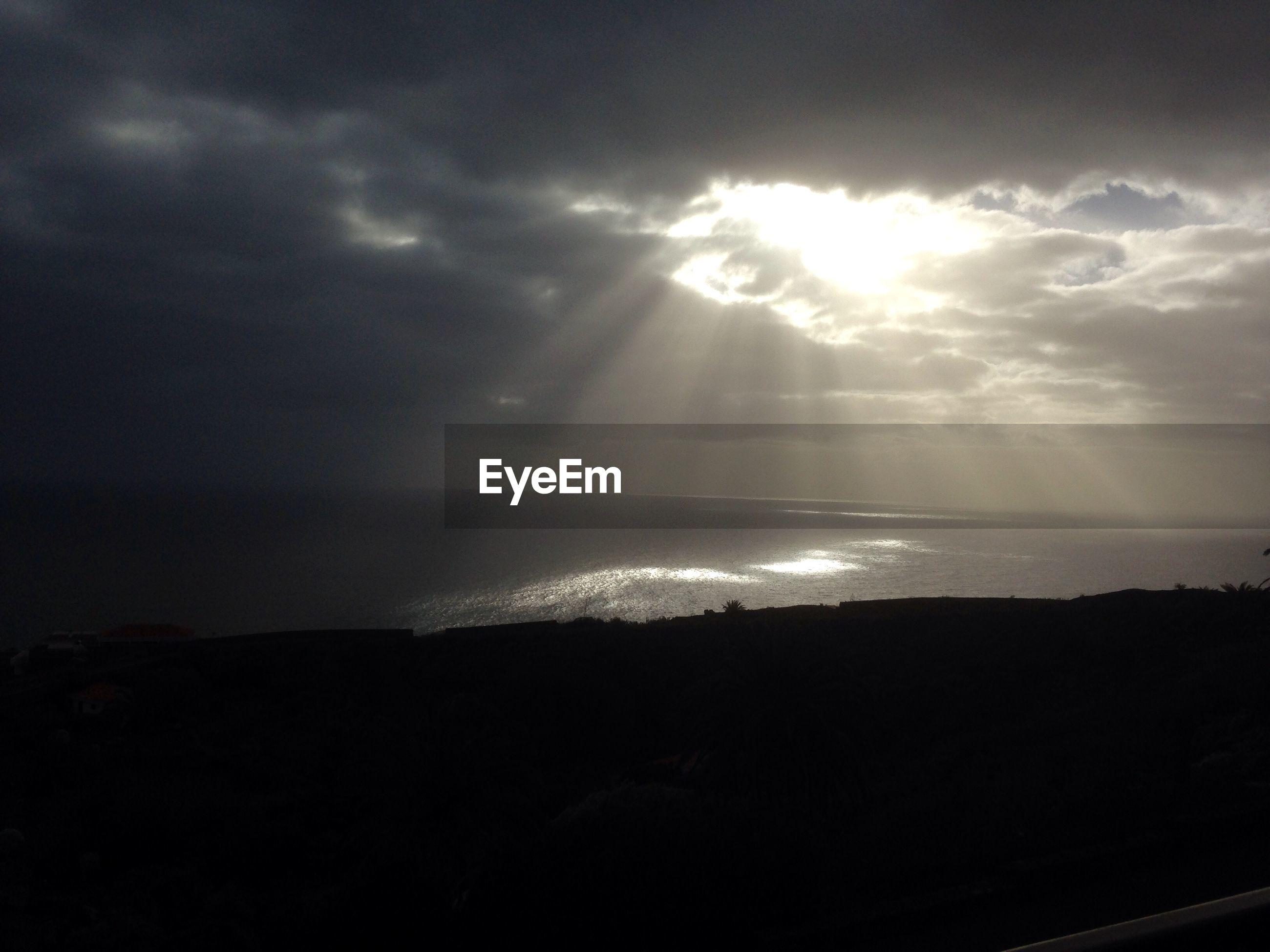 Sunlight emitting through clouds over sea