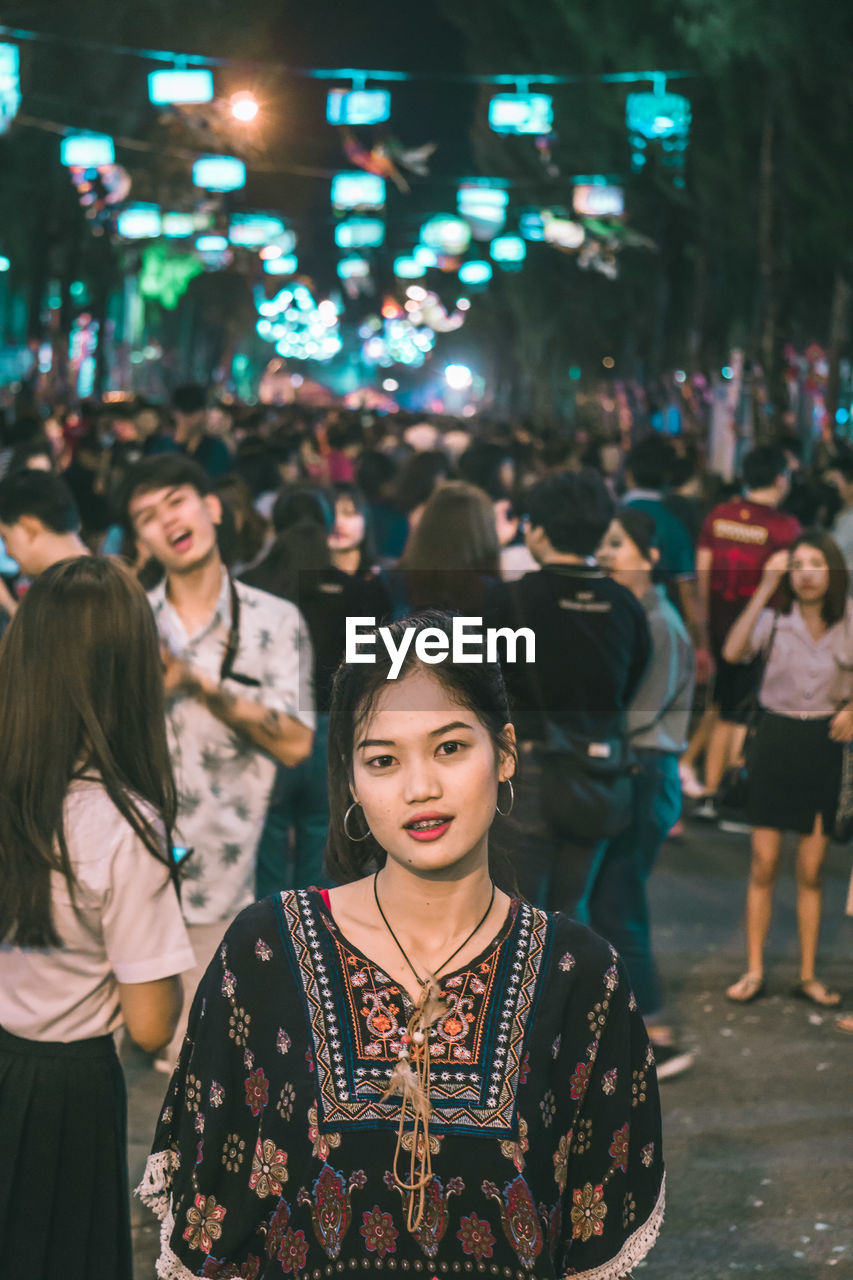 real people, group of people, lifestyles, people, young adult, women, standing, adult, leisure activity, focus on foreground, young women, illuminated, night, clothing, incidental people, event, traditional clothing, front view, portrait, beautiful woman, festival, nightlife