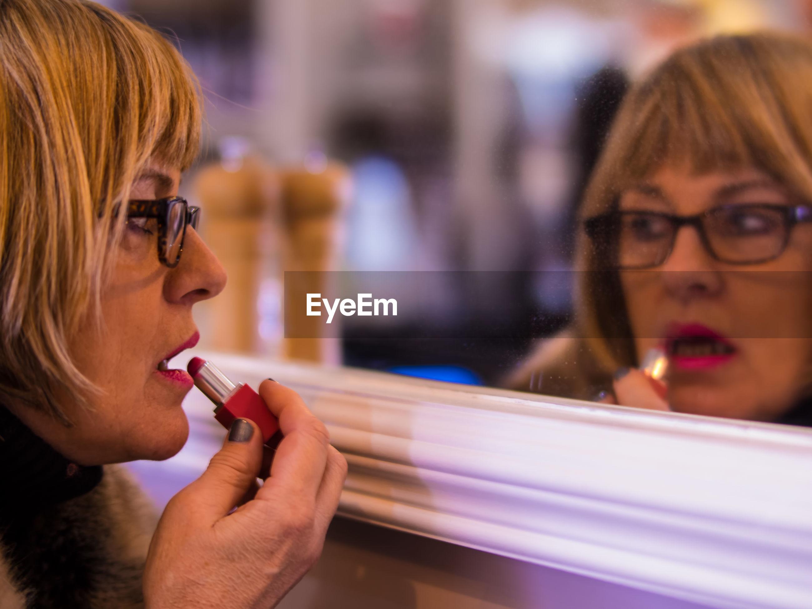 Close-up portrait of woman applying makeup