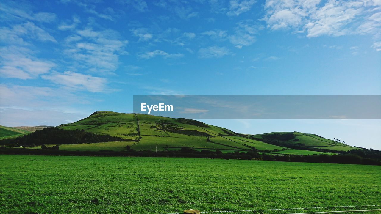 field, agriculture, tranquil scene, nature, beauty in nature, tranquility, landscape, scenics, no people, green color, sky, cloud - sky, day, rural scene, growth, outdoors, mountain, grass